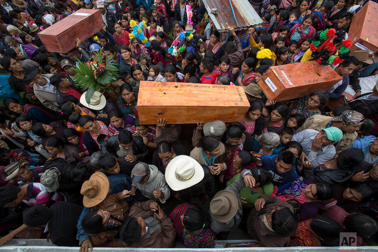 People carry coffins with the remains of civil war victims, to place in niche graves in Santa Avelina, Guatemala, Thursday, Nov. 30, 2017. After seven years of work by forensic anthropologists, including DNA tests to locate relatives, the remains of 172 indigenous Ixil Mayans killed during the civil war between 1978 and 1982 were buried in their community in the western mountains of Guatemala.  (AP Photo/Luis Soto)