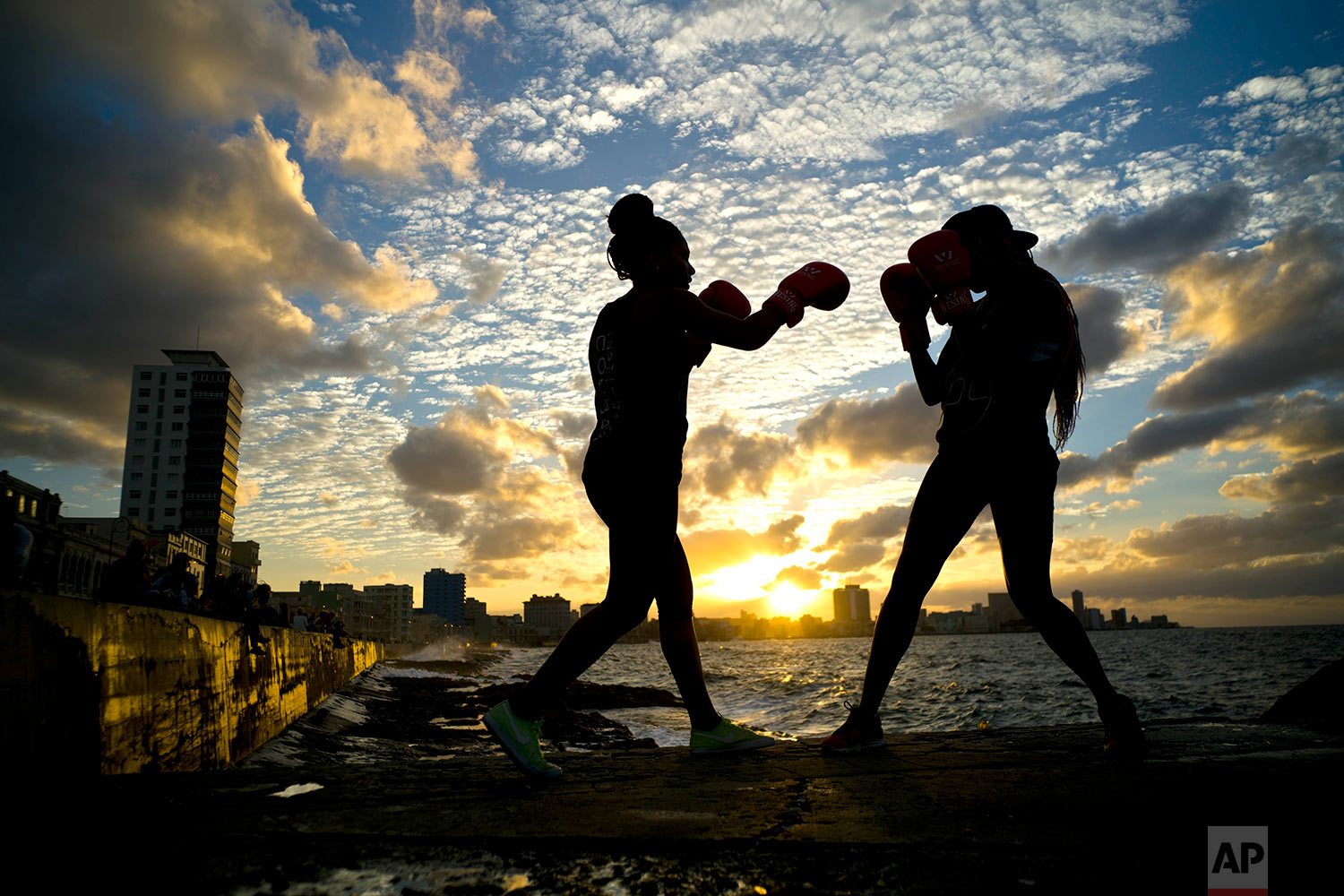 "In this Jan. 30, 2017 photo, boxers Idamerys Moreno, left, and Legnis Cala, train during a photo session on Havana's sea wall in Cuba. Moreno and Cala are part of a group of up-and-coming female boxers on the island who want government support to form Cuba's first female boxing team and help dispel a decades-old belief once summed up by a former top coach: ""Cuban women are meant to show the beauty of their face, not receive punches."" (AP Photo/Ramon Espinosa)"
