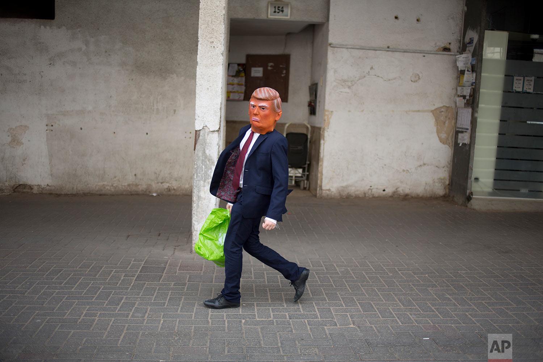 An Ultra-Orthodox Jewish child wears U.S. President Donald Trump's mask and costume during the Purim festival in Bnei Brak, near Tel Aviv, Israel, Sunday, March 12, 2017.(AP Photo/Ariel Schalit)