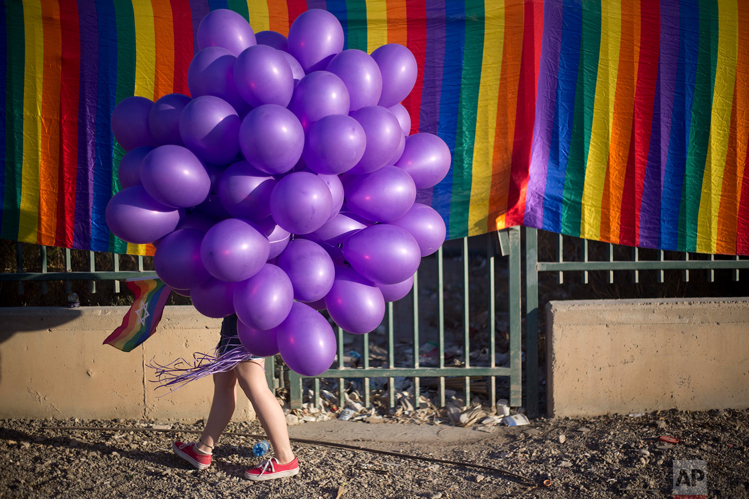 A woman holds balloons as she participates in the first Gay Pride Parade in Beersheba, Israel, Thursday, June 22, 2017. (AP Photo/Ariel Schalit)