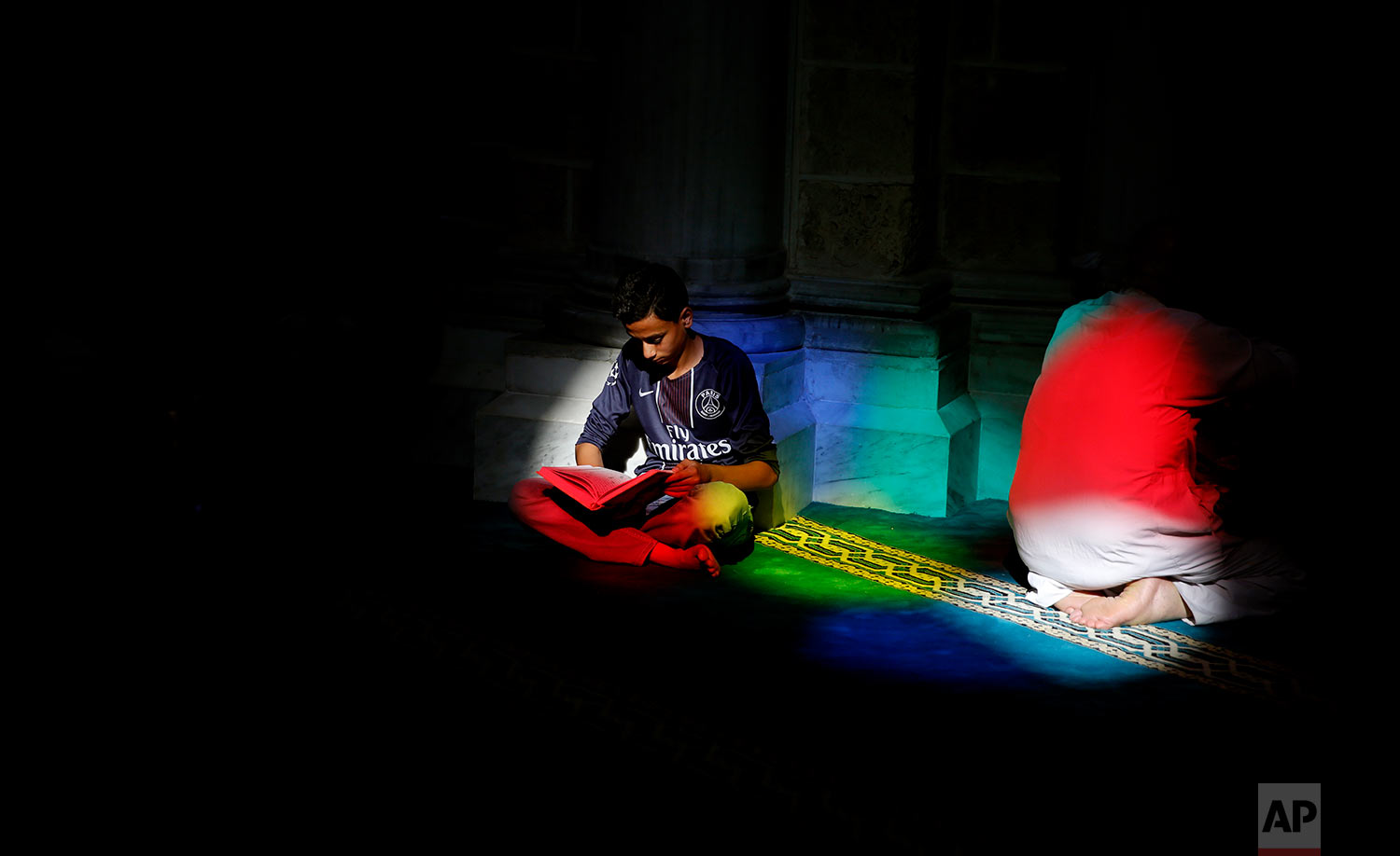 A Palestinian man reads verses of the Quran, Islam's holy book, during the month of Ramadan at Al Emari mosque in Gaza City, Monday, May 29, 2017. Muslims across the world are observing the holy fasting month of Ramadan, where they refrain from eating, drinking and smoking from dawn to dusk. (AP Photo/Hatem Moussa)