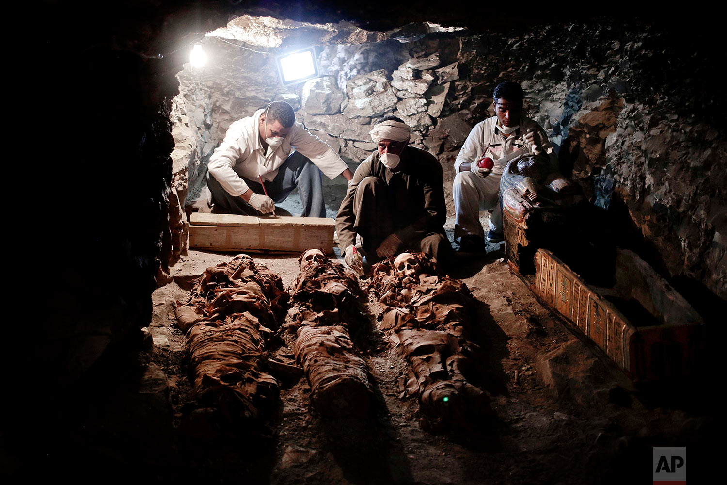 Archaeologists work on mummies found in the New Kingdom tomb that belongs to a royal goldsmith in a burial shaft, in Luxor, Egypt, Saturday, Sept. 9, 2017. Egypt has announced the discovery in the southern city of Luxor of a pharaonic tomb belonging to a royal goldsmith who lived more than 3,500 years ago during the reign of the 18th dynasty. (AP Photo/Nariman El-Mofty)