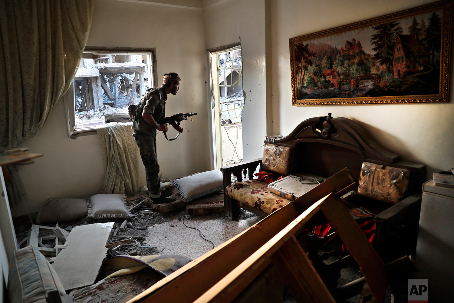 A U.S.-backed Syrian Democratic Forces fighter, looks through a window as he takes his position inside a destroyed apartment on the front line, in Raqqa city, northeast Syria, Thursday, July 27, 2017. (AP Photo/Hussein Malla)