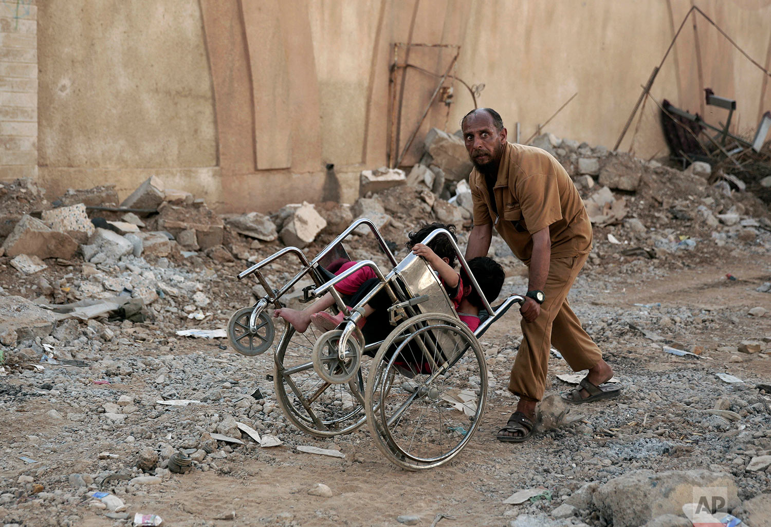 A man pushes two children in a wheelchair as they flee heavy fighting between Islamic State militants and Iraqi special forces in Mosul, Iraq, Wednesday, May 10, 2017. (AP Photo/Maya Alleruzzo)