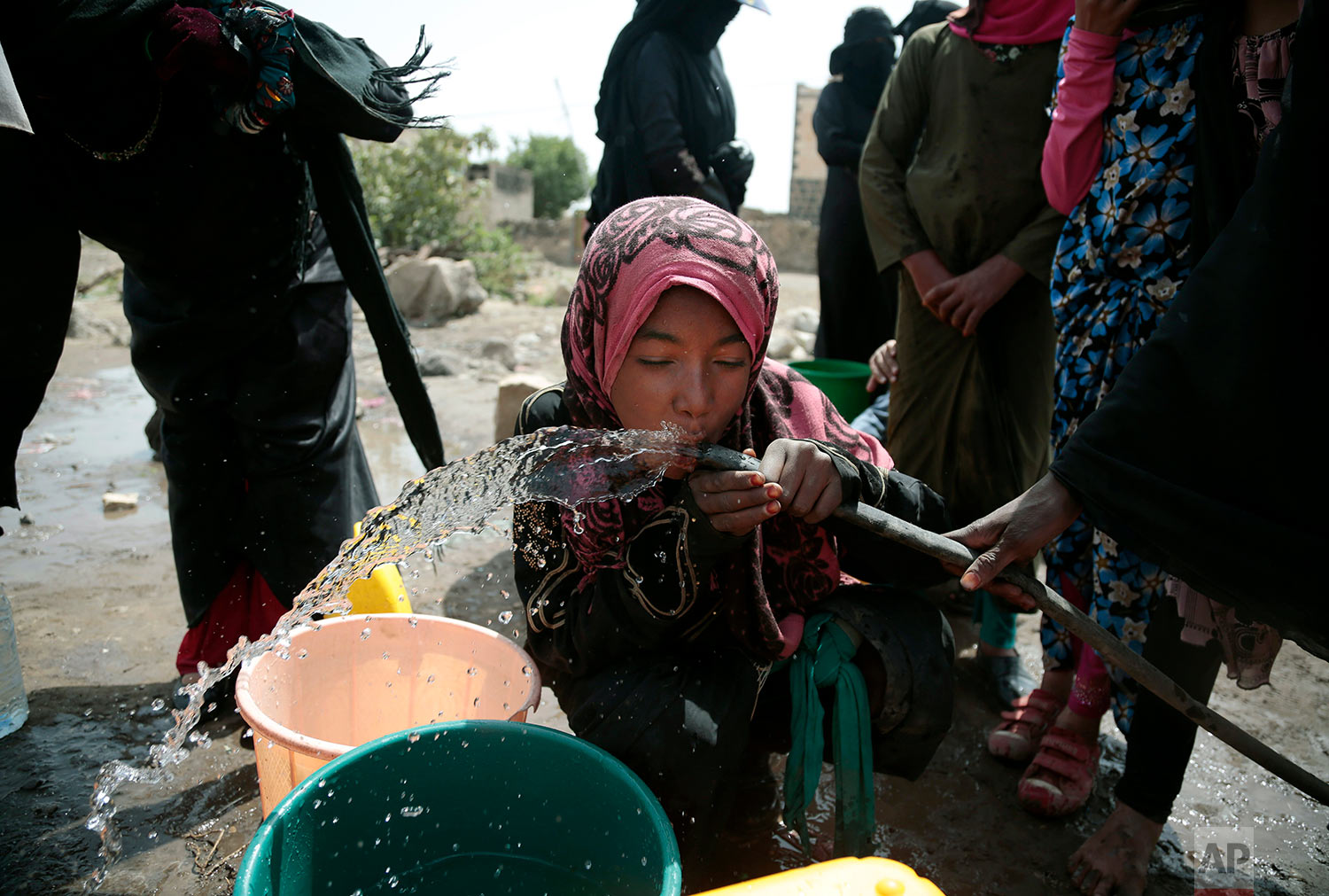 A girl drinks water from a well that alleged to be contaminated water with the bacterium Vibrio cholera, on the outskirts of Sanaa, Yemen on July 12, 2017. Yemen's raging two-year conflict has served as an incubator for lethal cholera. (AP Photo/Hani Mohammed)