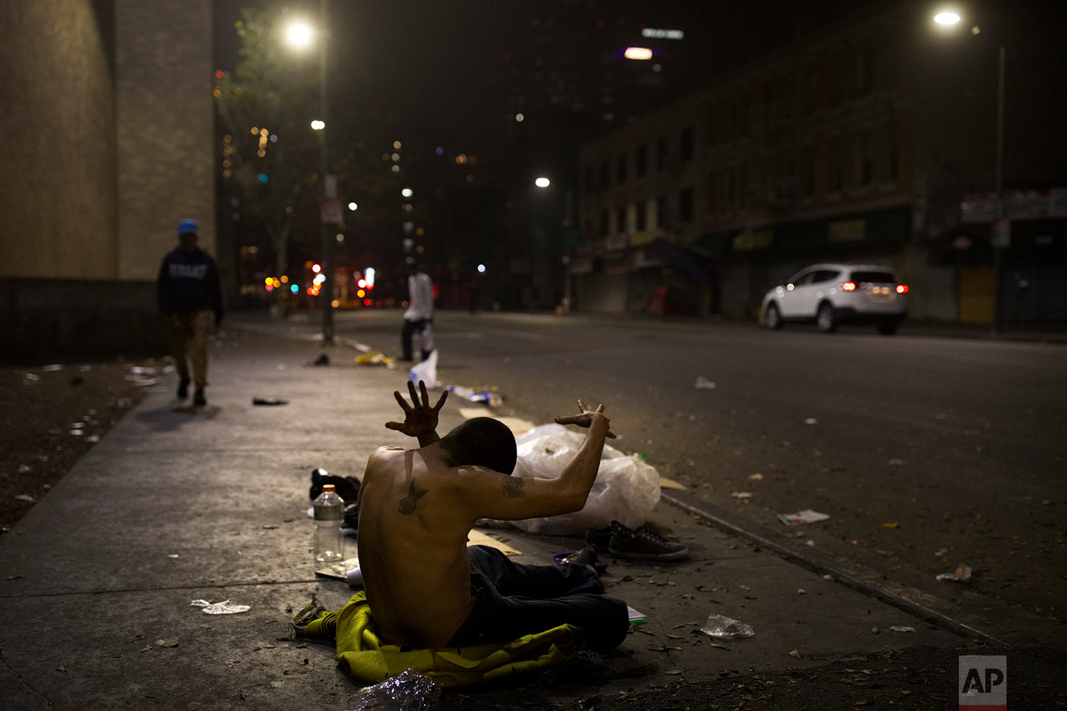 A homeless drug addict twists his body while sitting on a sidewalk Saturday, Oct. 28, 2017, in the Skid Row area of downtown Los Angeles. (AP Photo/Jae C. Hong)