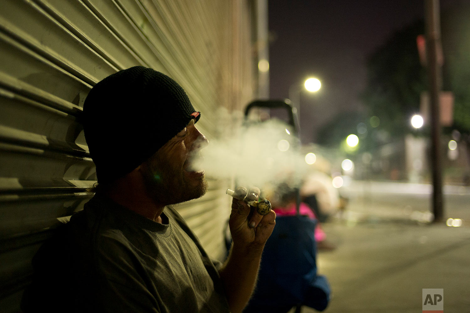 D. J. Meek, a 40-year-old homeless drug addict, smokes crystal meth Friday, Sept. 8, 2017, in the Skid Row area of downtown Los Angeles. Meeks' veins are collapsed due to chronic use of heroin. He said talking to himself makes him unemployable. (AP Photo/Jae C. Hong)