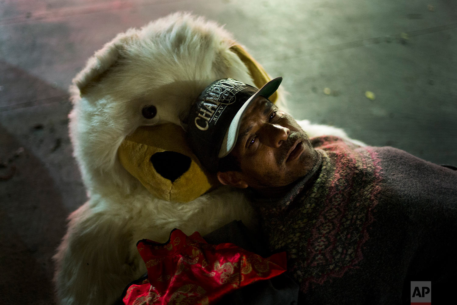 Using a teddy bear named Michelle as a pillow, Manuel Martinez, a 45-year-old homeless day laborer originally from Mexico, falls asleep on a sidewalk in the Skid Row area of downtown Los Angeles, Thursday, Nov. 2, 2017. Martinez said he has been an alcoholic more than a decade. (AP Photo/Jae C. Hong)