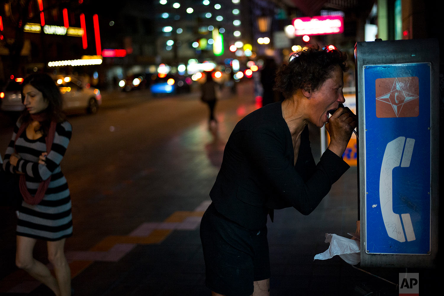 A mentally-ill homeless woman cries out while holding a pay phone after running through several blocks of downtown Los Angeles, yelling and screaming Saturday, Nov. 4, 2017. The woman, who said her name was Kara Miller when asked in September, is a Skid Row resident. Wandering around the streets where drugs rule, Miller talks to herself almost always and occasionally screams and curses as if seeing a ghost. (AP Photo/Jae C. Hong)