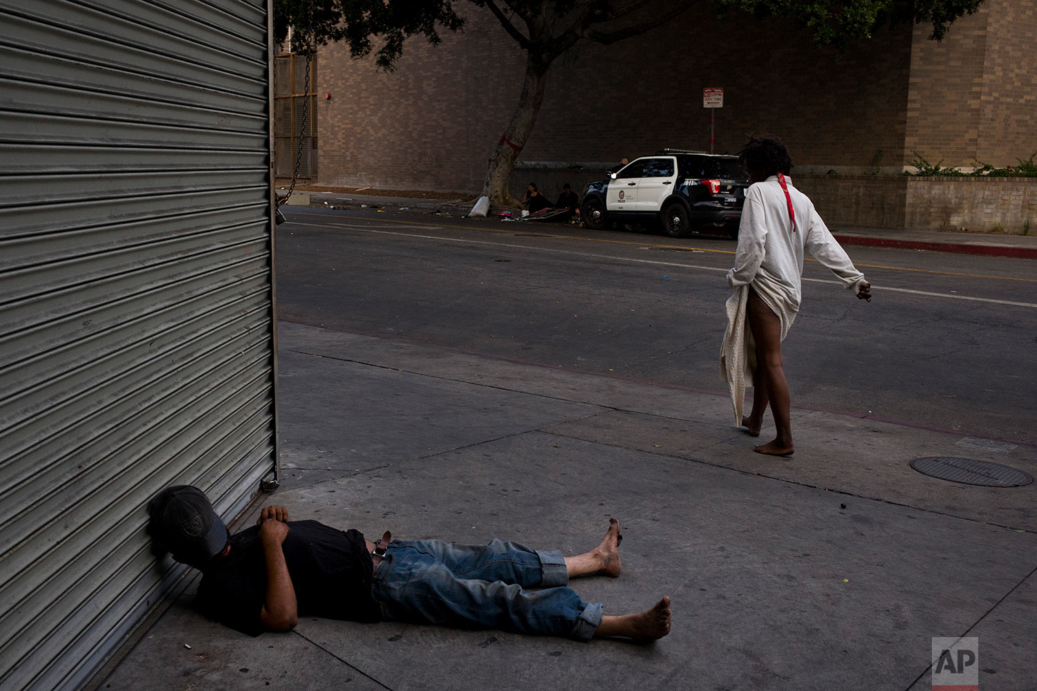 A mentally ill homeless woman walks past a man sleeping on a sidewalk in the Skid Row area of downtown Los Angeles, Friday, Sept. 1, 2017. (AP Photo/Jae C. Hong)