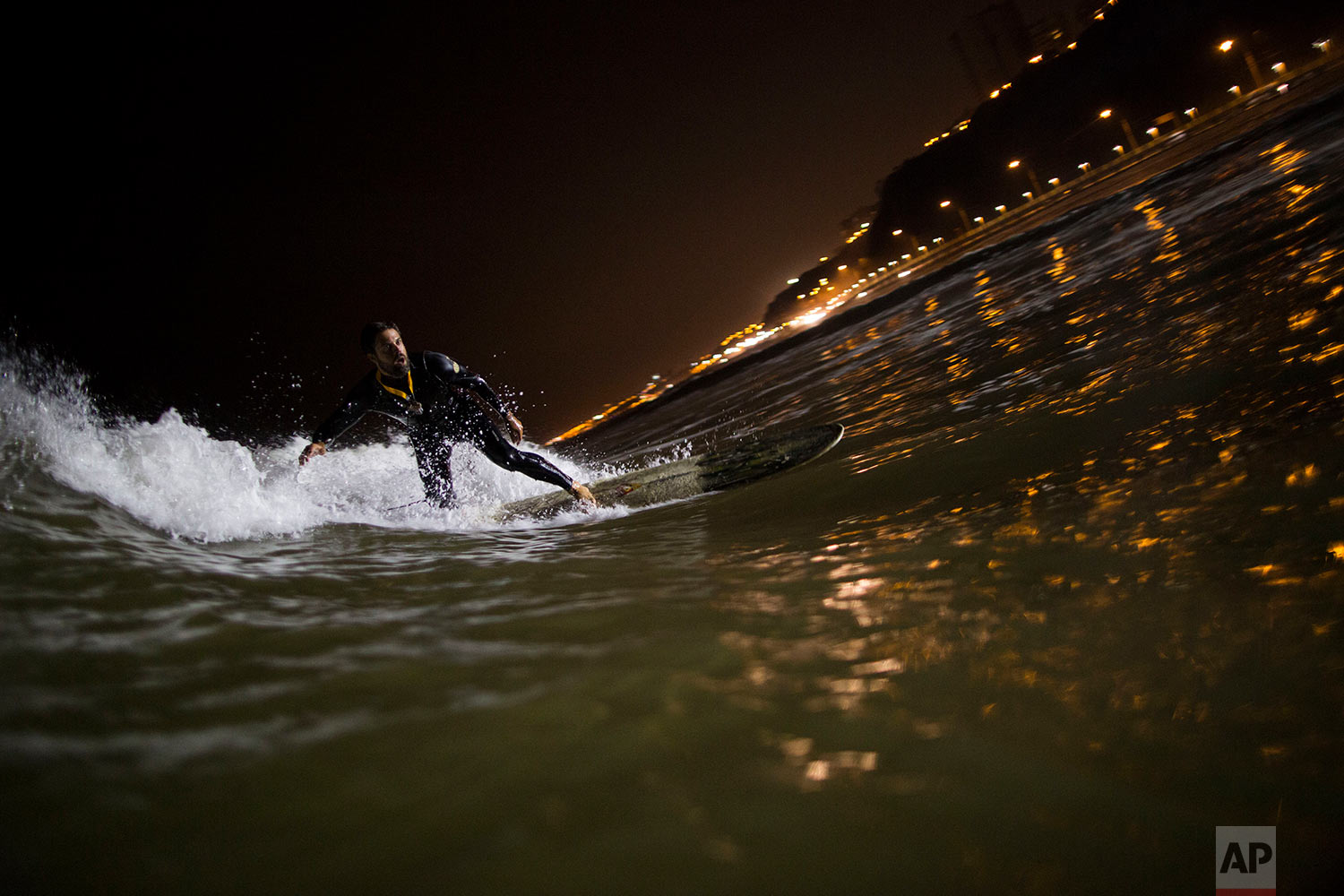 Ernesto Benavides rides a wave in the waters of La Pampilla beach in Lima, Peru, April 26, 2017. As most Lima residents prepare to sleep, a handful of hardcore surfers descend on the only beach in Peru where they can ride the waves at night. (AP Photo/Rodrigo Abd)
