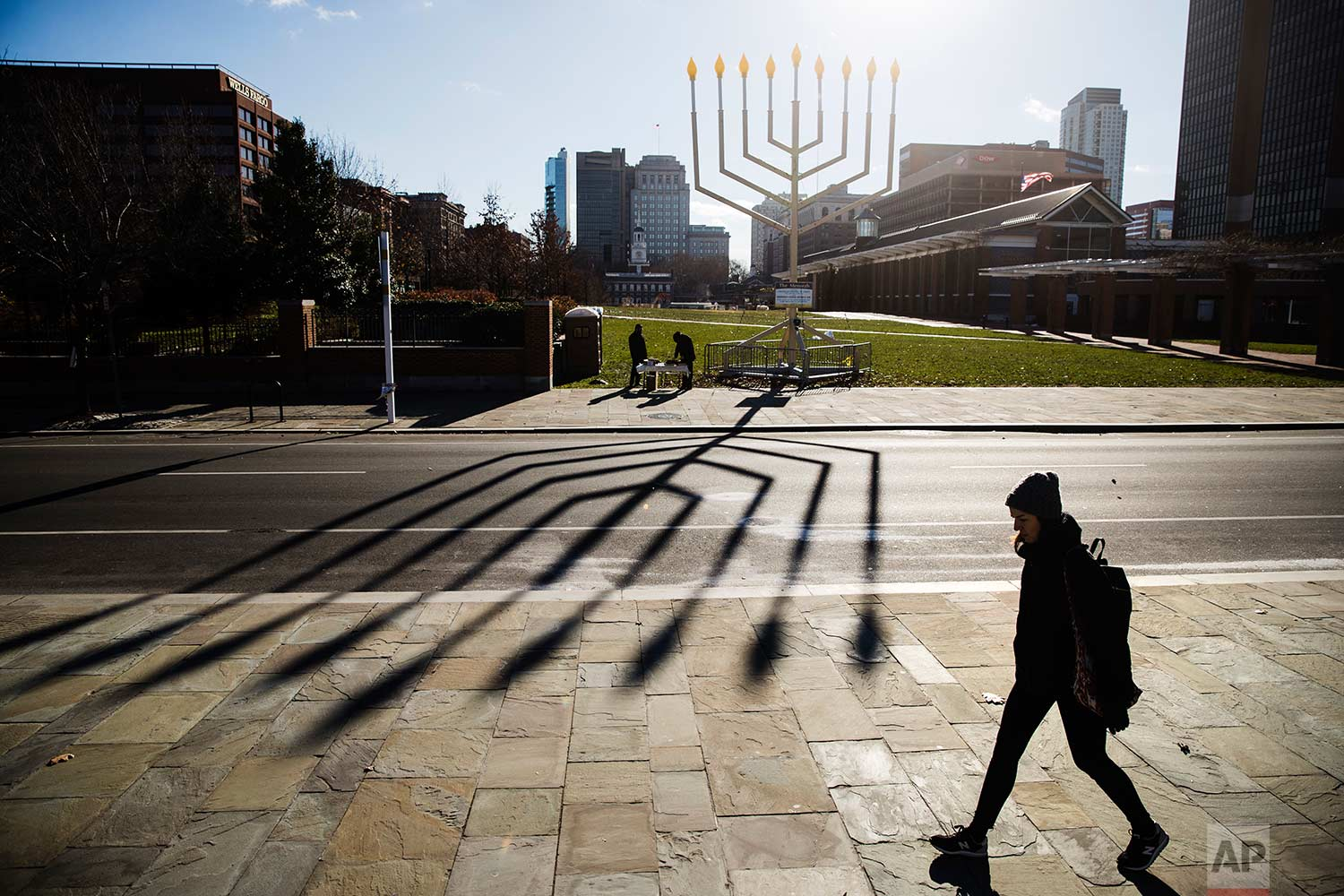 A woman passes by a menorah on Independence Mall in Philadelphia ahead of the second night of Hanukkah, Wednesday, Dec. 13, 2017. (AP Photo/Matt Rourke)