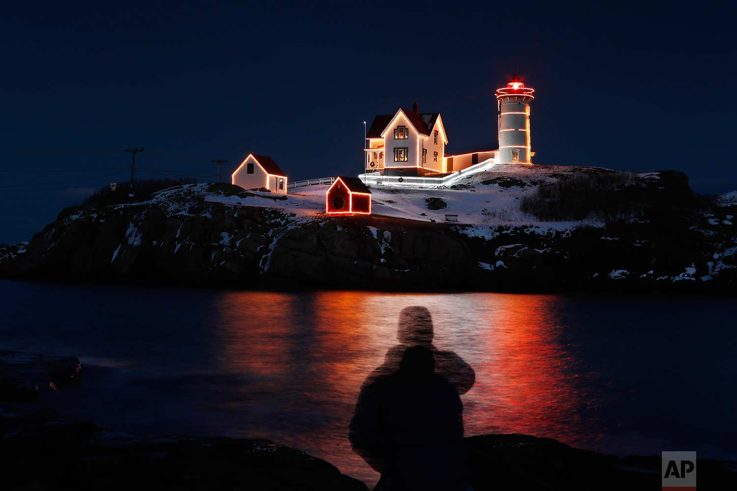 In this long exposure shot, holiday lights reflect in the waters off Nubble Light, silhouetting photographer Michael Blanchette of Bedford, N.H., Monday, Dec. 11, 2017, in York, Maine. (AP Photo/Robert F. Bukaty)