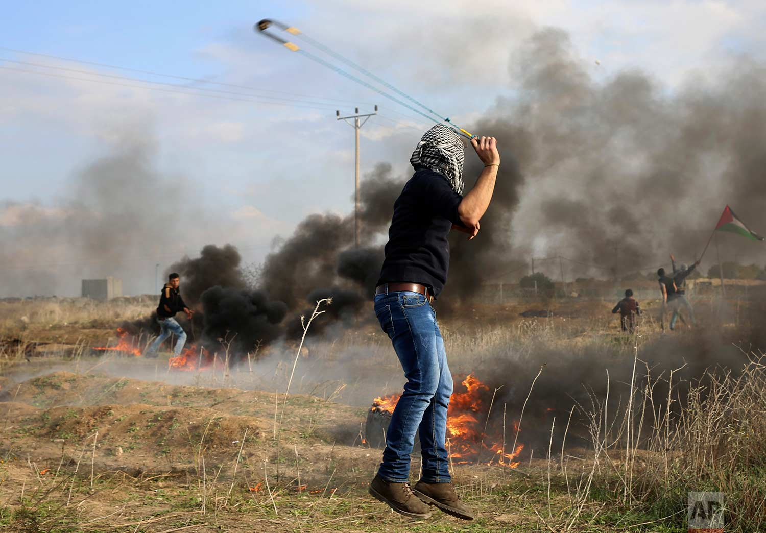 A Palestinian protester slings stones towards Israeli soldiers during clashes on the Israeli border following a protest against U.S. President Donald Trump's decision to recognize Jerusalem as the capital of Israel, east of Gaza City, Friday, Dec. 15, 2017. (AP Photo/Adel Hana)