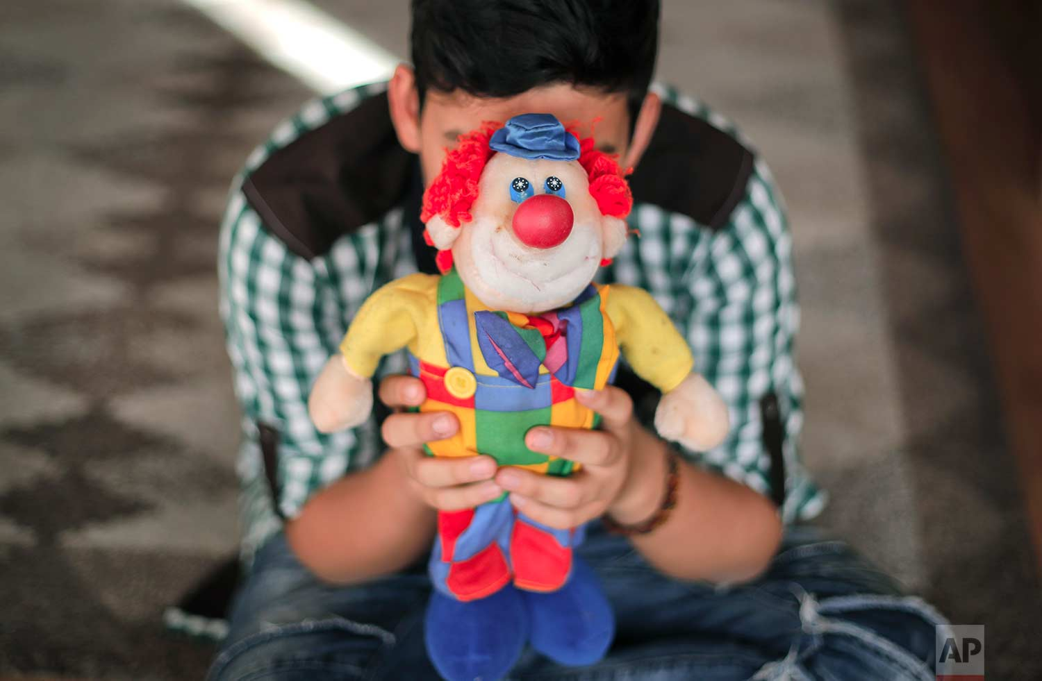 A boy living in a family-style home for abandoned children poses for a photo covering his face with a clown doll in Bucharest, Romania, on Wednesday, Nov. 1, 2017. (AP Photo/Vadim Ghirda)