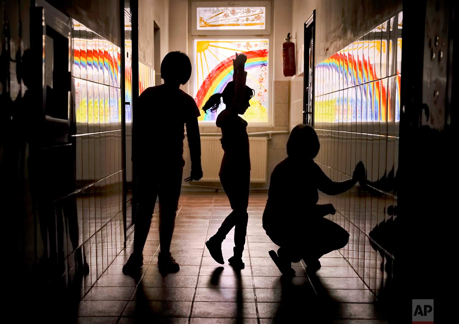 Sara, a child living at the Robin Hood orphanage, tries a ballet move while posing for a photo with other children in a corridor with painted windows, in Bucharest, Romania, on Friday, Nov. 3, 2017. (AP Photo/Vadim Ghirda)