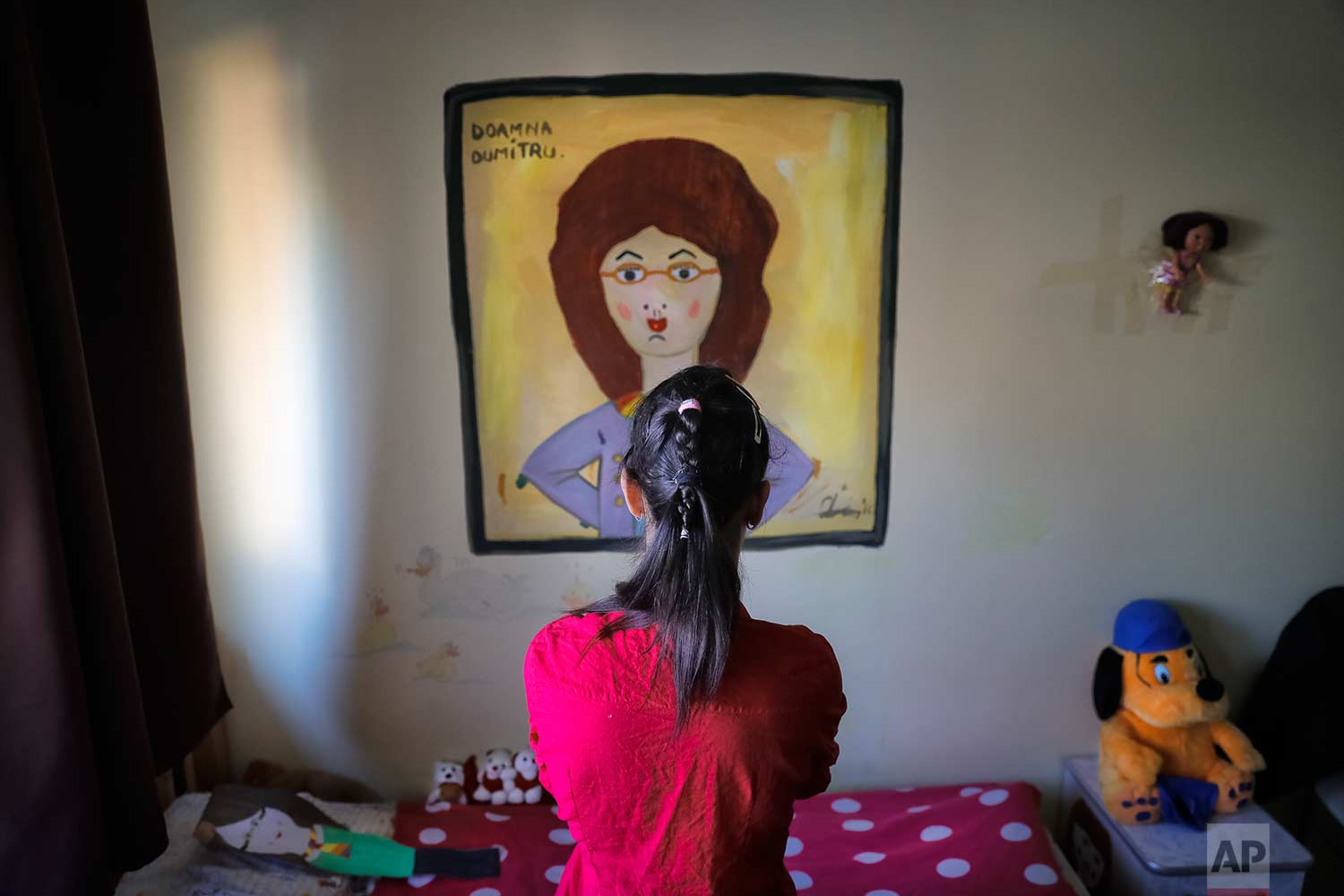 Elena, a girl living in a family style home with 10 other youths, poses for a photo in front of a painting of one of her teachers, in Bucharest, Romania, Wednesday, Nov. 1, 2017. (AP Photo/Vadim Ghirda)