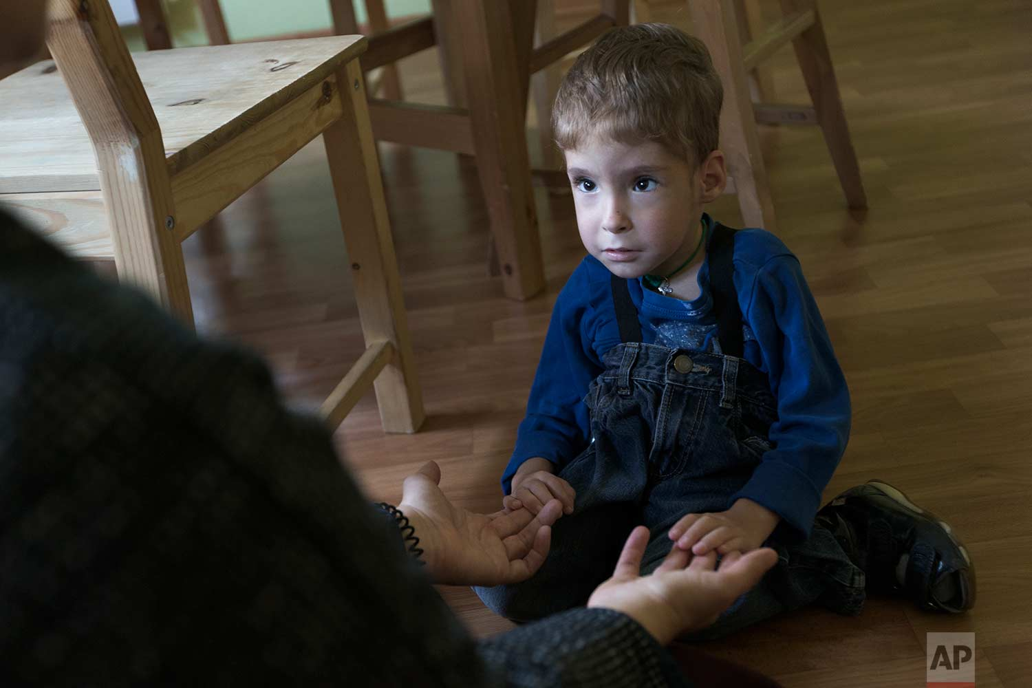 Volunteer Yelizaveta, left, looks at 4-year-old pupil, Syoma, at the St. Sophia orphanage in Moscow, Russia, on Tuesday, Sept. 12, 2017. (AP Photo/Ivan Sekretarev)