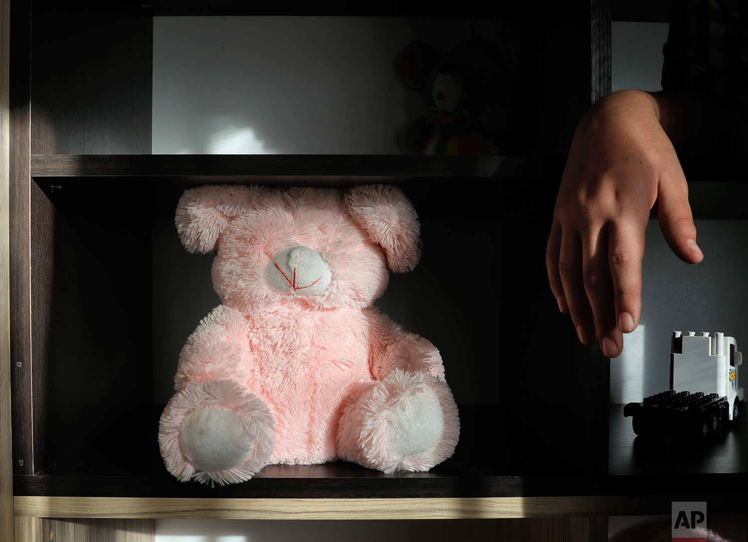A boy stands next to a teddy bear missing its eyes at a foster home in Bucharest, Romania, on Wednesday, Nov. 1, 2017. (AP Photo/Vadim Ghirda)