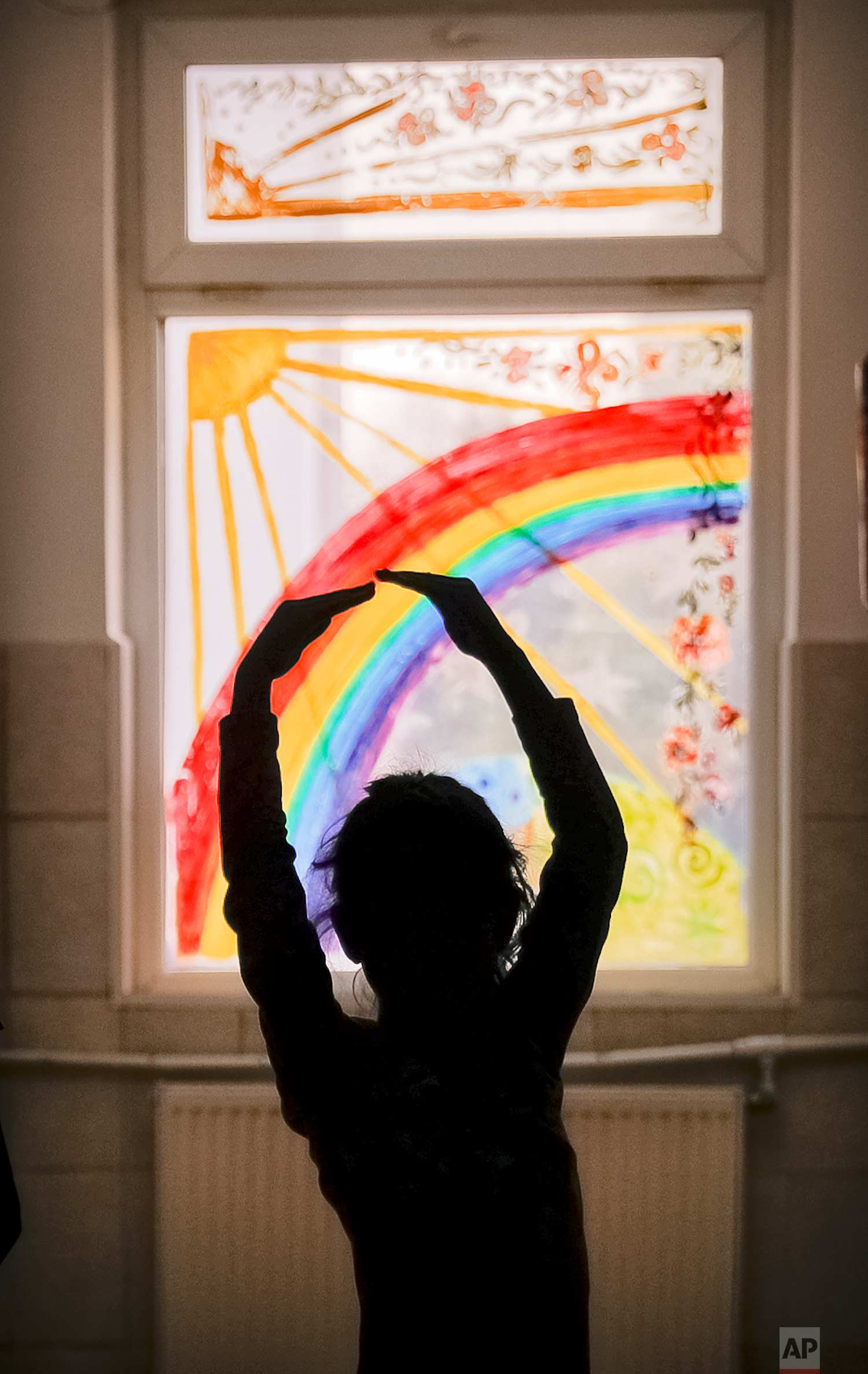 Sara, a child living at the Robin Hood orphanage, tries a ballet move while posing on a corridor with painted windows, in Bucharest, Romania, on Friday, Nov. 3, 2017. (AP Photo/Vadim Ghirda)