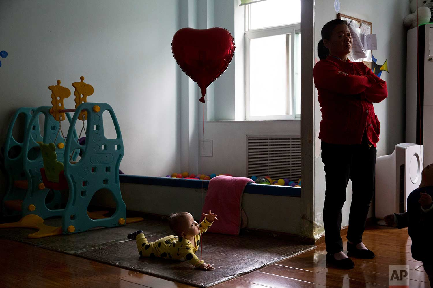 A child reaches towards a minder at a foster home of the New Hope Foundation, a charity that provides care and medical treatment for babies with deformities that can be corrected with surgery, on the outskirts of Beijing, China, on Wednesday, Oct. 11, 2017. (AP Photo/Ng Han Guan)