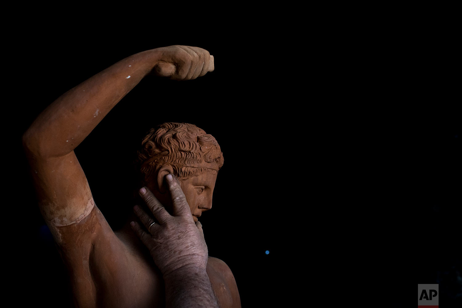 In this Tuesday, Dec. 19, 2017 photo, sculptor and ceramicist Haralambos Goumas touches a terracotta statue of Hermes, messenger of the ancient Greek gods, at his workshop in the Egaleo suburb of Athens. (AP Photo/Petros Giannakouris)