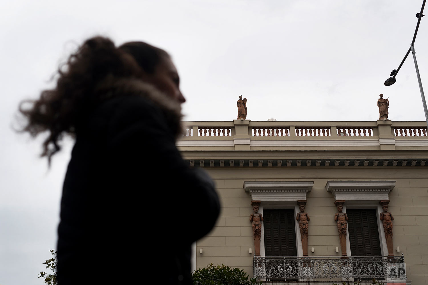 In this Thursday, Dec. 21, 2017 photo, a woman walks past a neoclassical building decorated with terracotta statues of the muses, on the roof, and Atlases, flanking the windows, made by sculptor and ceramicist Haralambos Goumas in Piraeus, the port of Athens. (AP Photo/Petros Giannakouris)