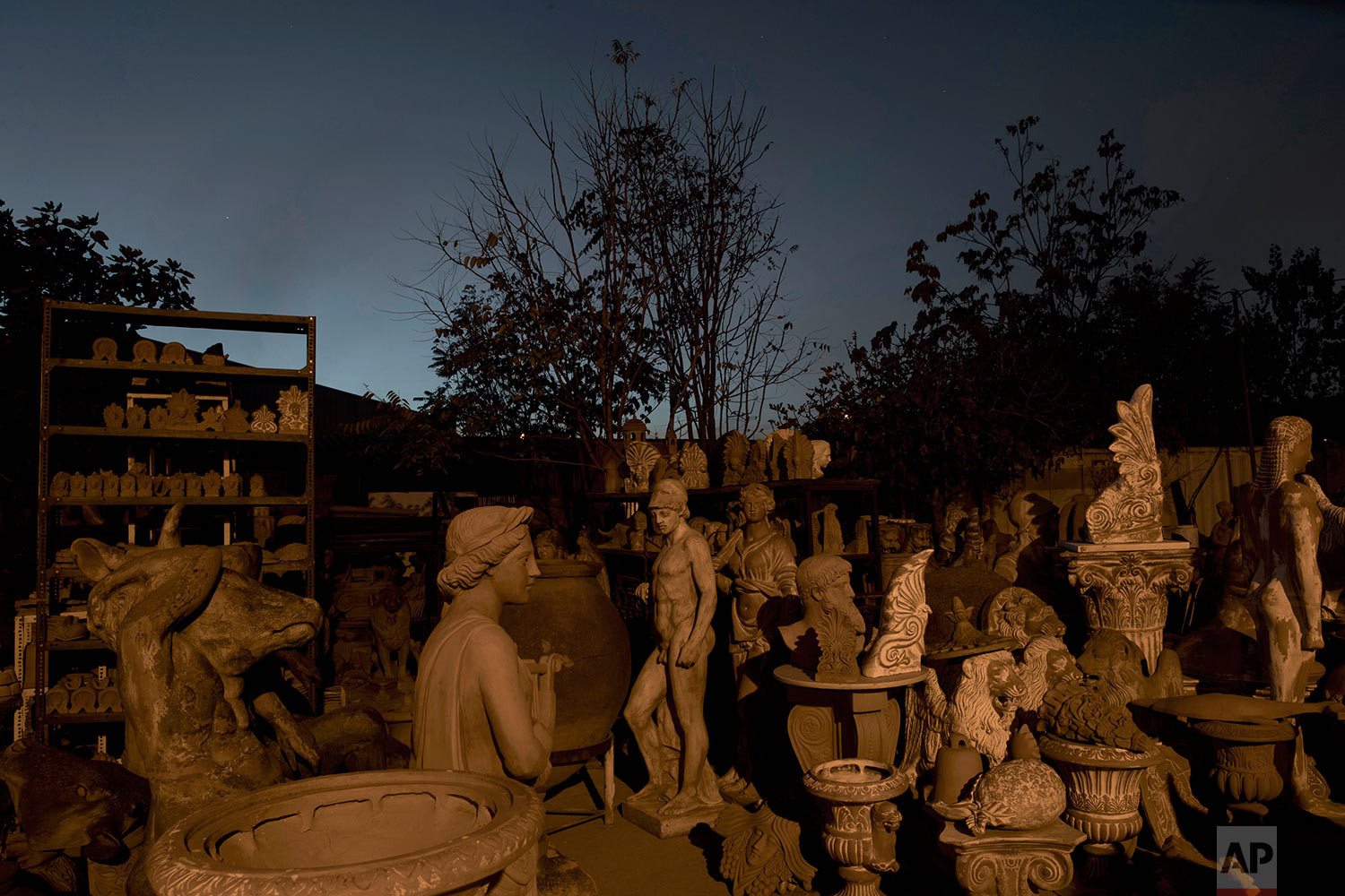 In this Friday, Nov. 20, 2017 photo, the terracotta statue of Ares, the ancient Greek god of war, middle, stands among other statues, busts, antefixes and flowers pots in the yard of Haralambos Goumas' sculpture and ceramic workshop, in the Egaleo suburb of Athens. (AP Photo/Petros Giannakouris)