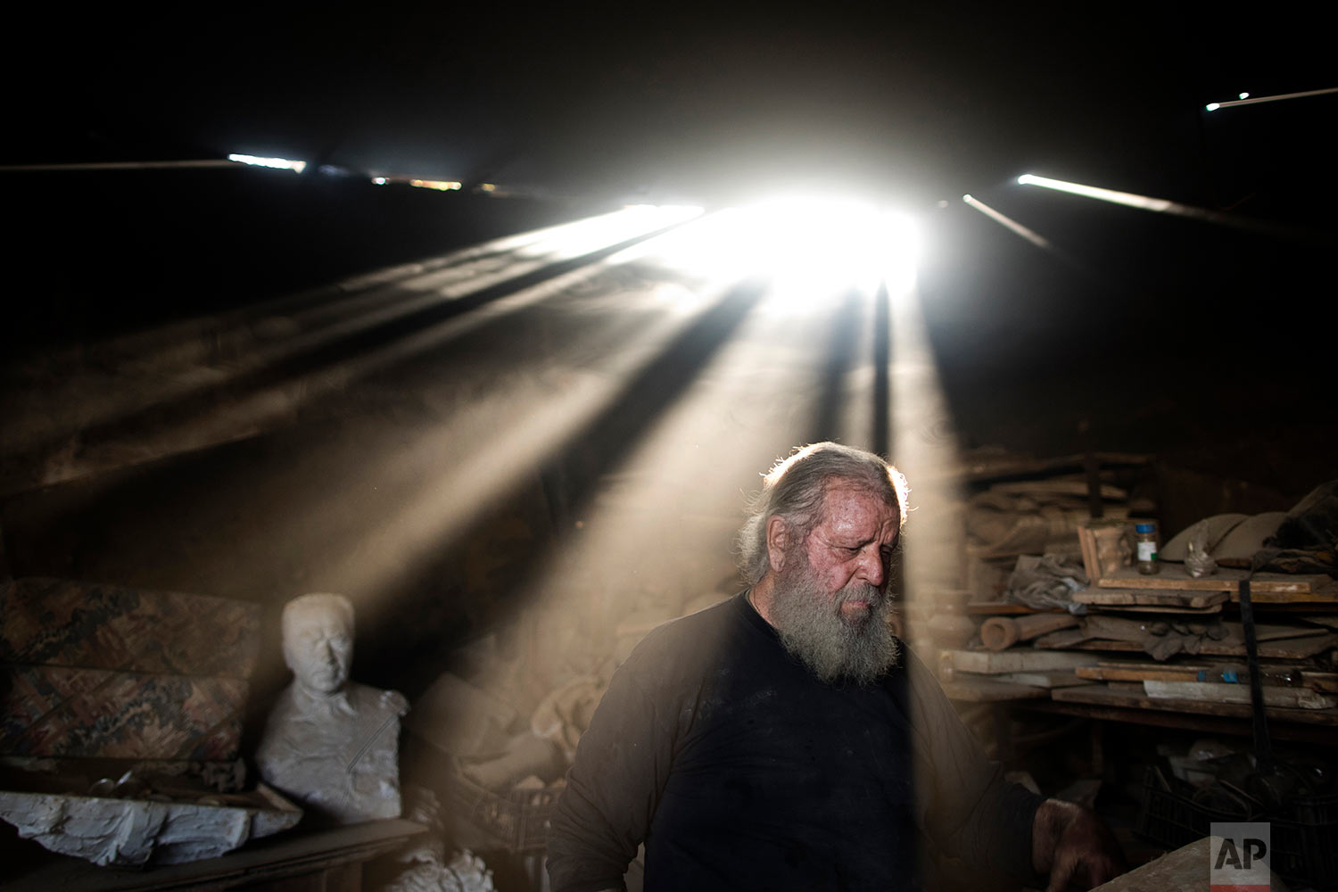 In this Friday, Nov. 20, 2017 photo, rays of sunlight shine on sculptor and ceramicist Haralambos Goumas as he works in his workshop, in the Egaleo suburb of Athens. (AP Photo/Petros Giannakouris)
