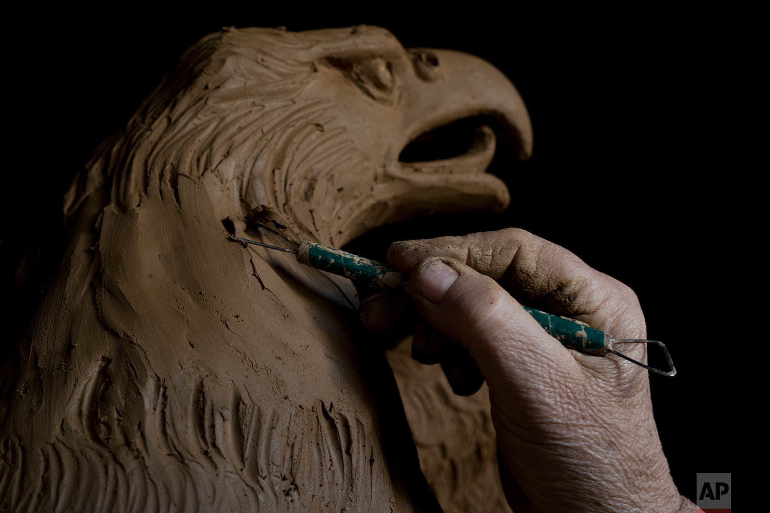 In this Tuesday, Nov. 14, 2017 photo, sculptor and ceramicist Haralambos Goumas works on a terracotta eagle, at his workshop, in the Egaleo suburb of Athens. (AP Photo/Petros Giannakouris)
