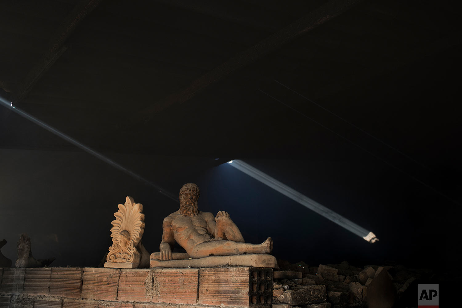 In this Friday, Nov. 20, 2017 photo, a sooty, dust-covered terracotta statue of Greek mythological hero Hercules, a son of Zeus, stands on top of a burning furnace next to an antefix in Haralambos Goumas' sculpture and ceramic workshop, in the Egaleo suburb of Athens. (AP Photo/Petros Giannakouris)