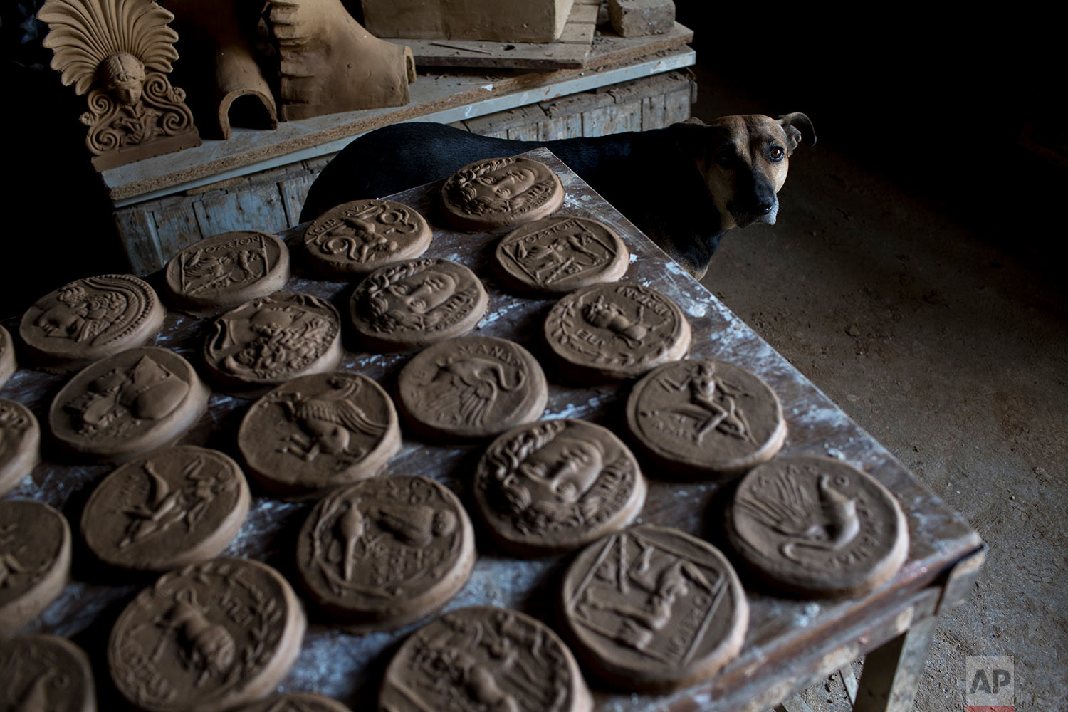 In this Friday, Oct. 13, 2017 photo a dog stands next to ceramic medallions based on ancient Greek coins in Haralambos Goumas' sculpture and ceramic workshop, in the Egaleo suburb of Athens. (AP Photo/Petros Giannakouris)