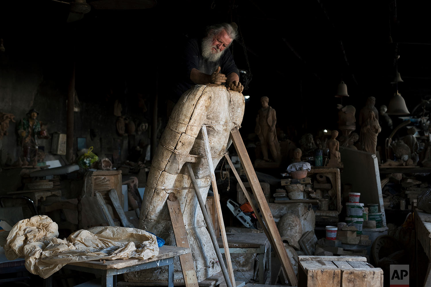 In this Thursday, Oct. 19, 2017 photo, sculptor and ceramicist Haralambos Goumas works on a huge terracotta eagle in a mould, at his workshop, in the Egaleo suburb of Athens.  (AP Photo/Petros Giannakouris)