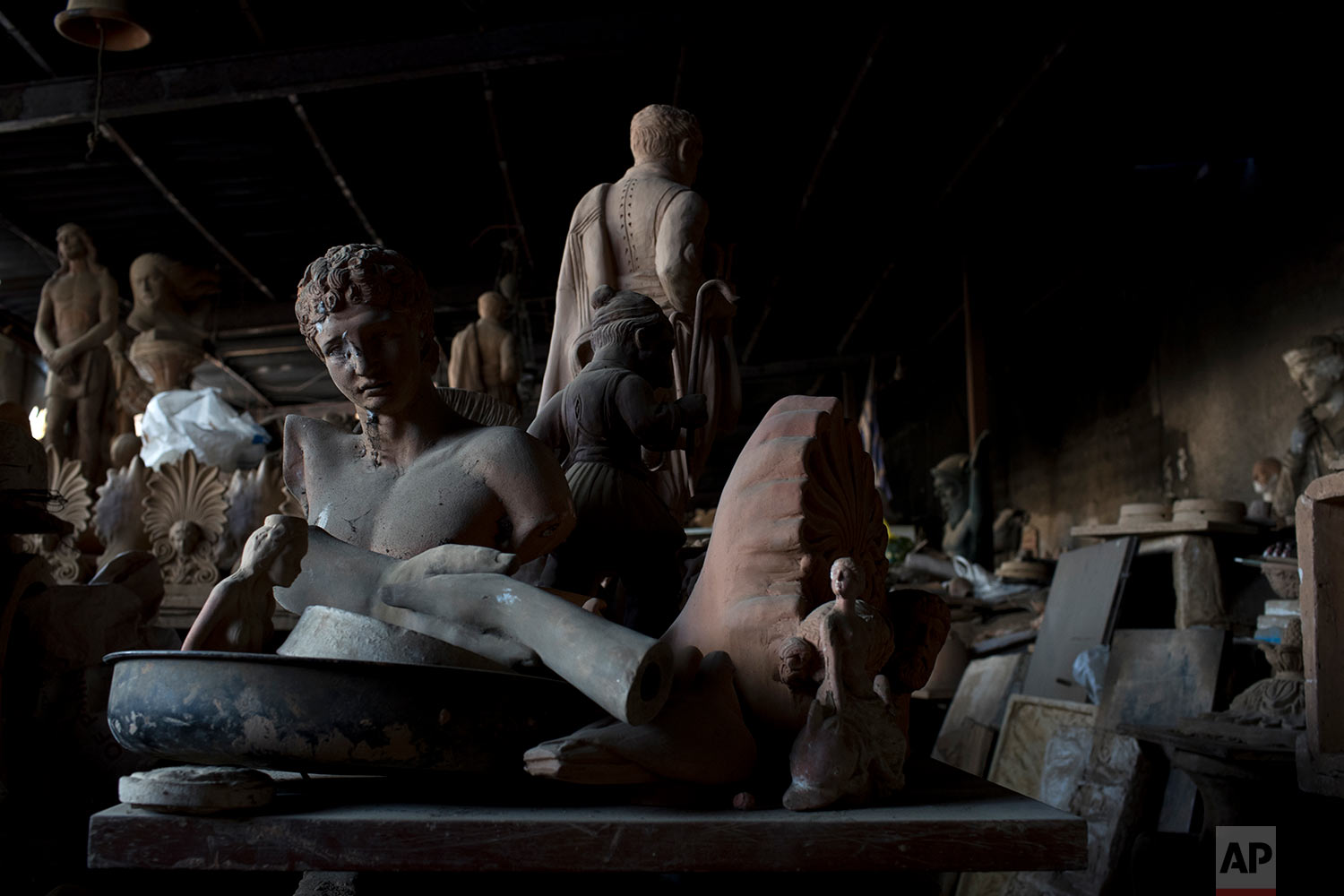 In this Friday, Oct. 13, 2017 photo, the bust of the ancient Greek messenger of the gods, Hermes, left, stands among other statues and antefixes in Haralambos Goumas' sculpture and ceramic workshop, in the Egaleo suburb of Athens. (AP Photo/Petros Giannakouris)