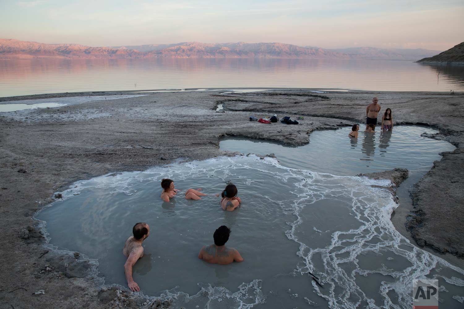 In this Friday, Nov. 24, 2017 photo, people enjoy a spring water pool along the Dead Sea shore near the Israeli Kibbutz of Ein Gedi. (AP Photo/Oded Balilty)
