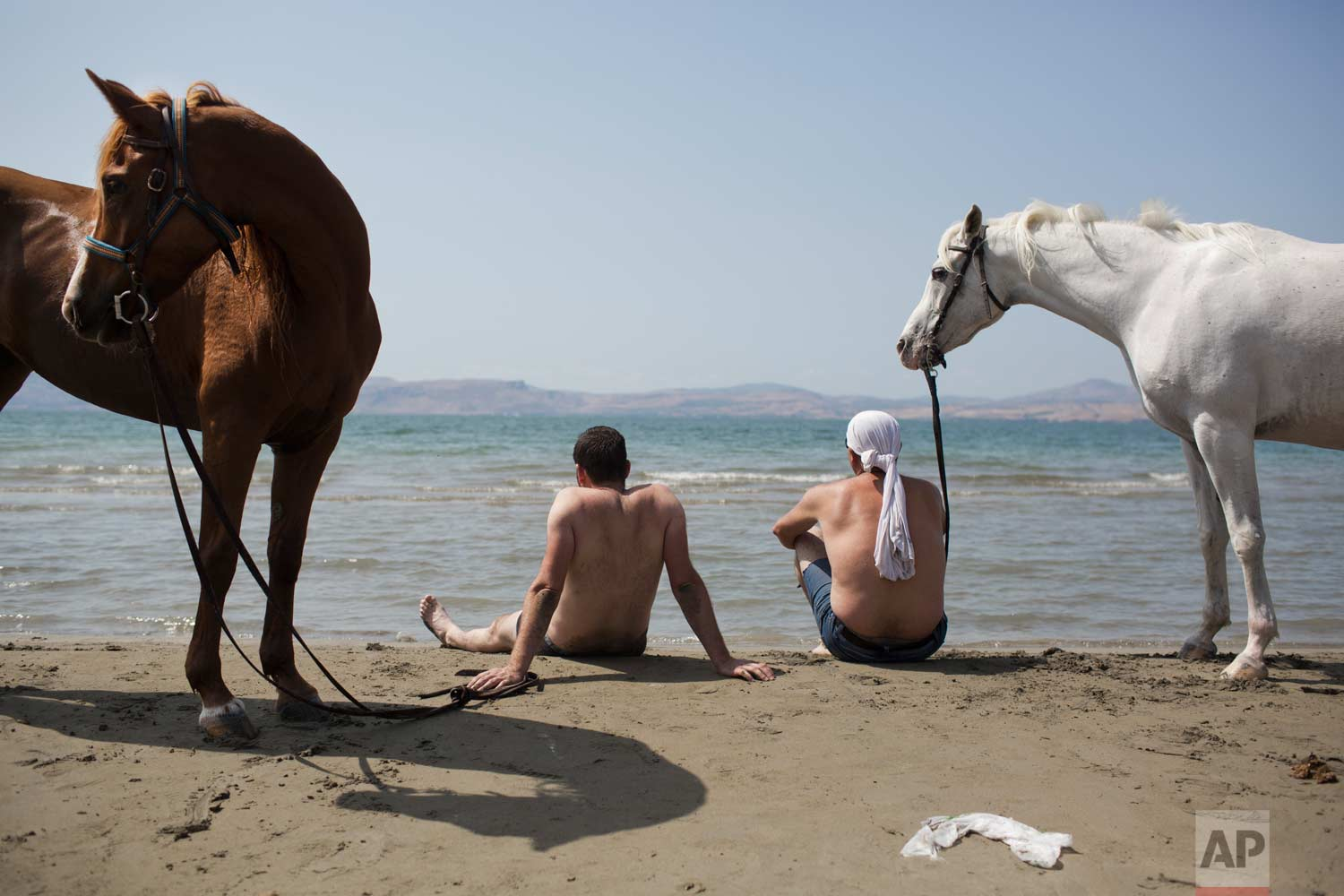 In this Saturday, Sept. 23, 2017 photo, Israeli Druse men sit with their horses on the shores of the Sea of Galilee near the northern Israeli Kibbutz of Ein Gev. (AP Photo/Oded Balilty)