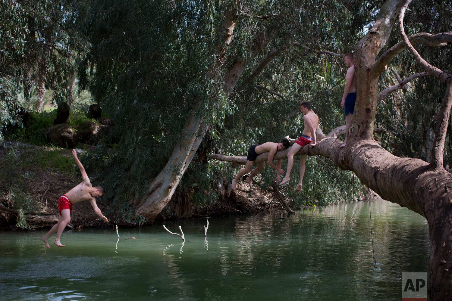 In this April 11, 2017 photo, Israelis jump into the Jordan River near the northern Israeli Kibbutz of Kinneret. (AP Photo/Oded Balilty)