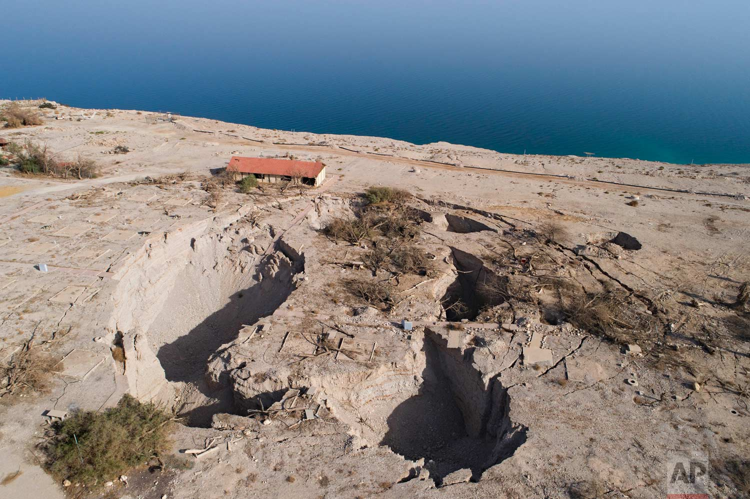In this Nov. 28, 2017 photo, an aerial view shows sinkholes in the abandoned tourist resort of Ein Gedi on the Dead Sea shore. (AP Photo/Oded Balilty)