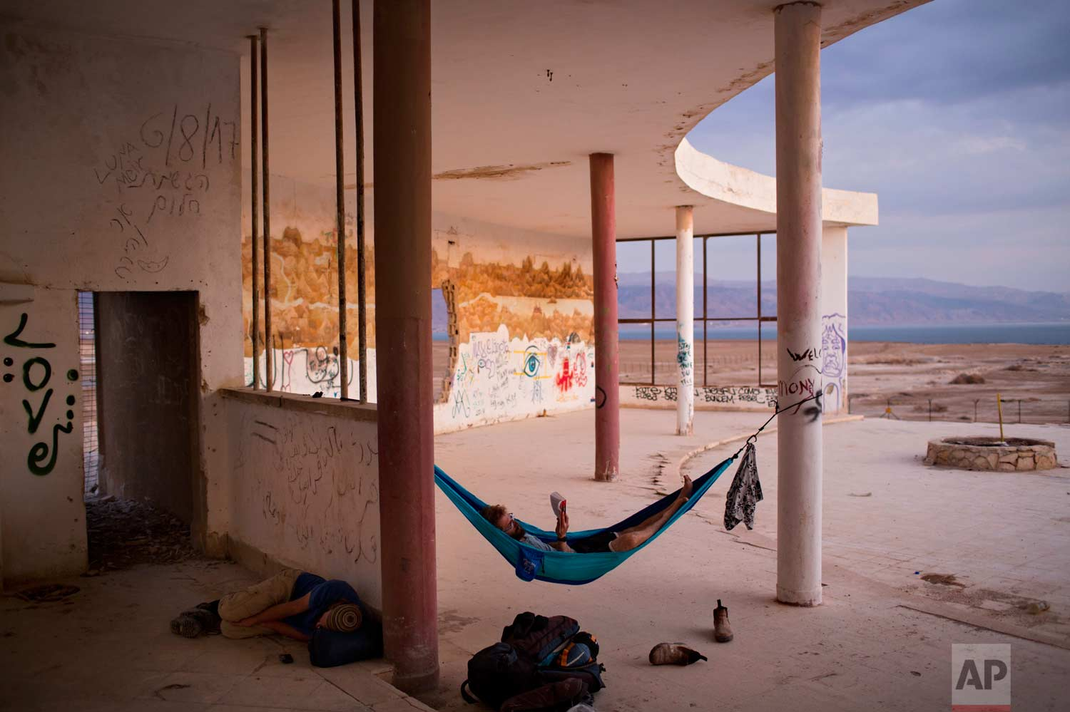 In this Oct. 16, 2017 photo, Israelis camp out in an abandoned restaurant overlooking the Dead Sea near Kibbutz Kalya. (AP Photo/Oded Balilty)