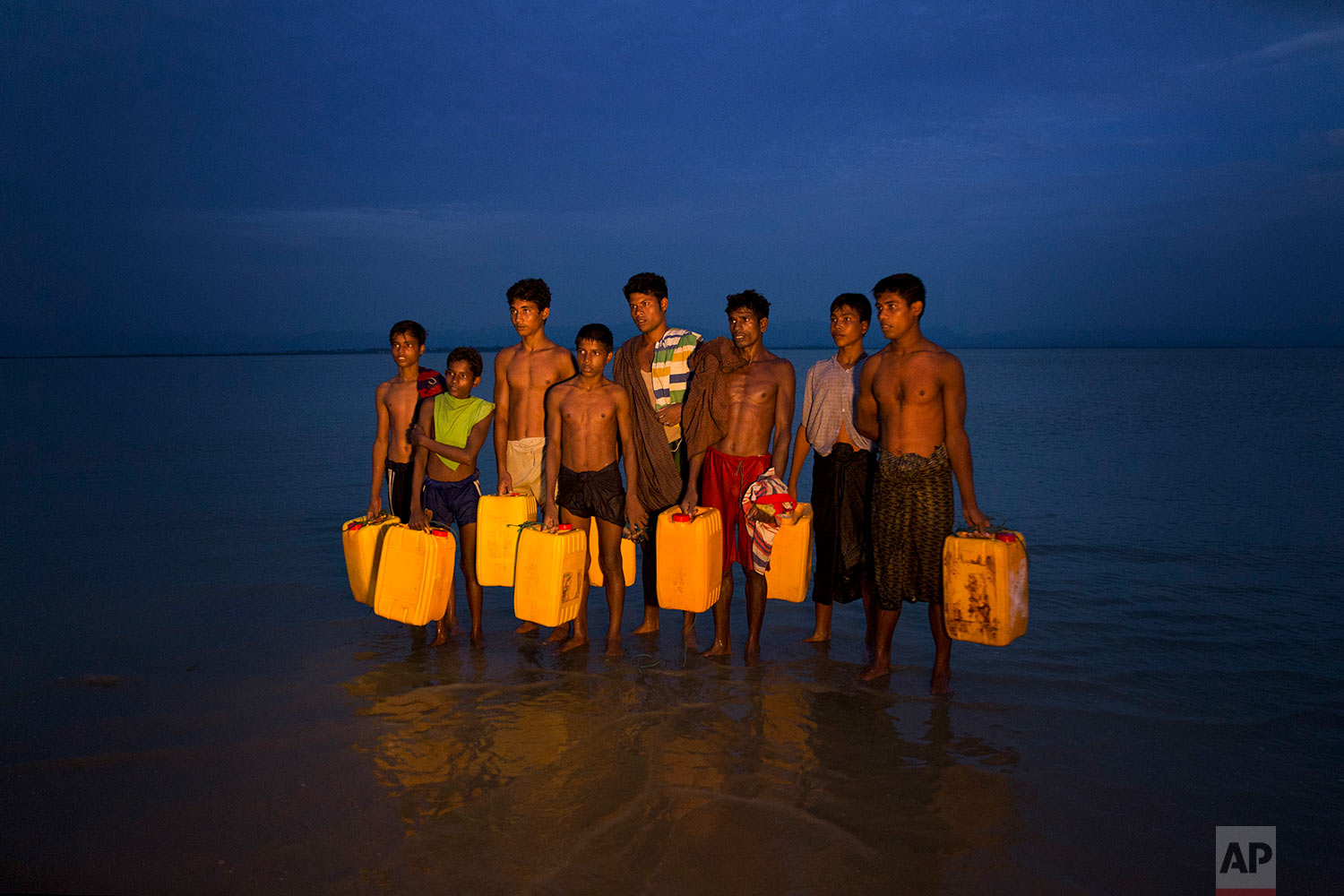 In this Nov. 5, 2017, photo, newly arrived Rohingya Muslims carry yellow plastic drums they used as flotation aids and listen to Bangladeshi authorities, not pictured, after swimming across the Naf river at Shah Porir Dwip, Bangladesh. The Naf river is a natural border between Myanmar and Bangladesh. Several young Rohingya Muslims escaping the violence in their homeland of Myanmar are now so desperate that they are swimming to safety into neighboring Bangladesh. (AP Photo/Bernat Armangue)