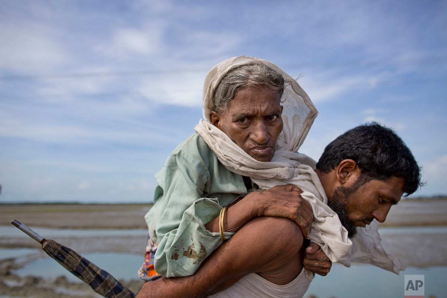 A Rohingya Muslim man carries an elderly woman and walks towards a camp for refugees after crossing over the border from Myanmar into Bangladesh in Teknaf, Bangladesh, Friday, Sept. 29, 2017. More than a month after Myanmar's refugees began spilling across the border, the U.N. says more than half a million have arrived. (AP Photo/Gemunu Amarasinghe)