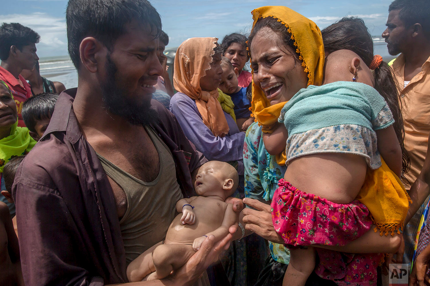 A Rohingya Muslim man Naseer Ud Din holds his infant son Abdul Masood, who drowned when the boat they were traveling in capsized just before reaching the shore, as his wife Hanida Begum cries upon reaching the Bay of Bengal shore in Shah Porir Dwip, Bangladesh, Thursday, Sept. 14, 2017. Nearly three weeks into a mass exodus of Rohingya fleeing violence in Myanmar, thousands were still flooding across the border Thursday in search of help and safety in teeming refugee settlements in Bangladesh. (AP Photo/Dar Yasin)
