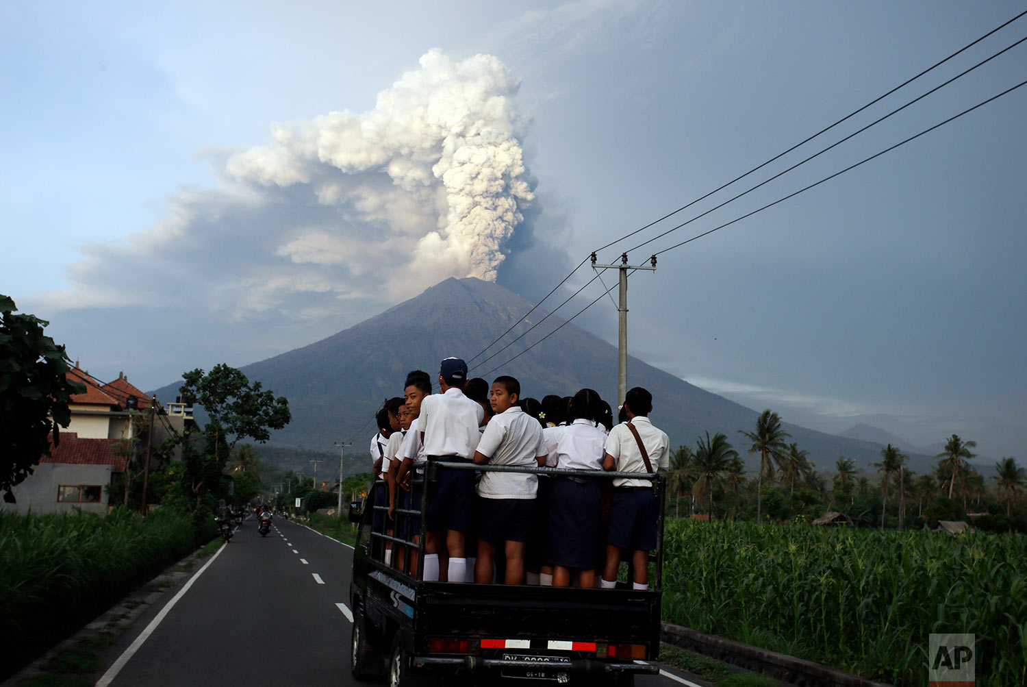 School students stand on a truck as their transport to go to school with the Mount Agung volcano spews smoke and ash in Karangasem, Bali, Indonesia, Tuesday, Nov. 28, 2017. Indonesia authorities raised the alert for the rumbling volcano to highest level on Monday and closed the international airport on the tourist island of Bali stranding some thousands of travelers.(AP Photo/Firdia Lisnawati)