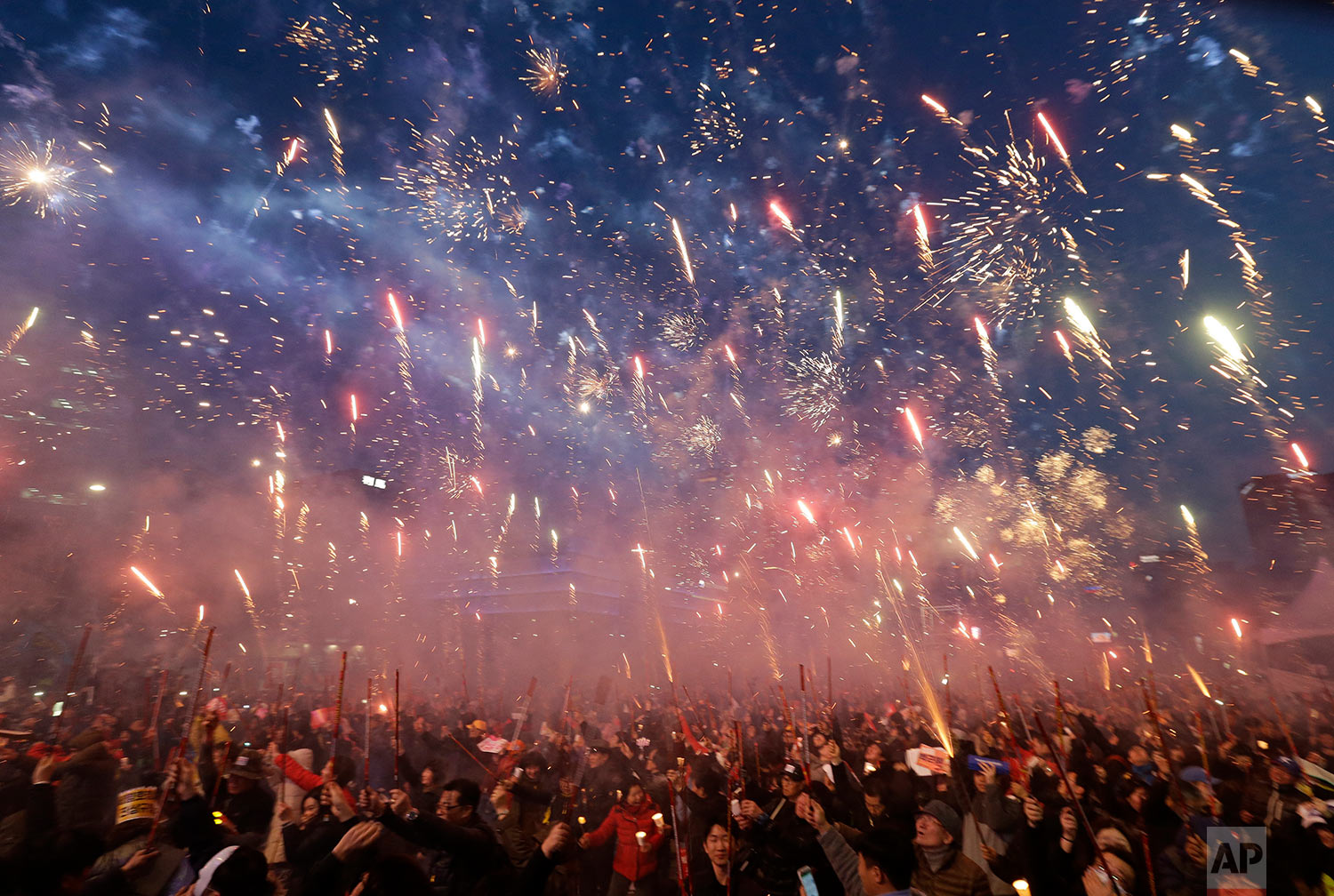 Protesters set off fireworks during a candle light vigil calling for impeached President Park Geun-hye's arrest in Seoul, South Korea, Saturday, March 11, 2017. South Korean police on Saturday braced for more violence between opponents and supporters of ousted President Park Geun-hye, who was stripped of her powers by the Constitutional Court over a corruption scandal that has plunged the country into a political turmoil. (AP Photo/Ahn Young-joon)