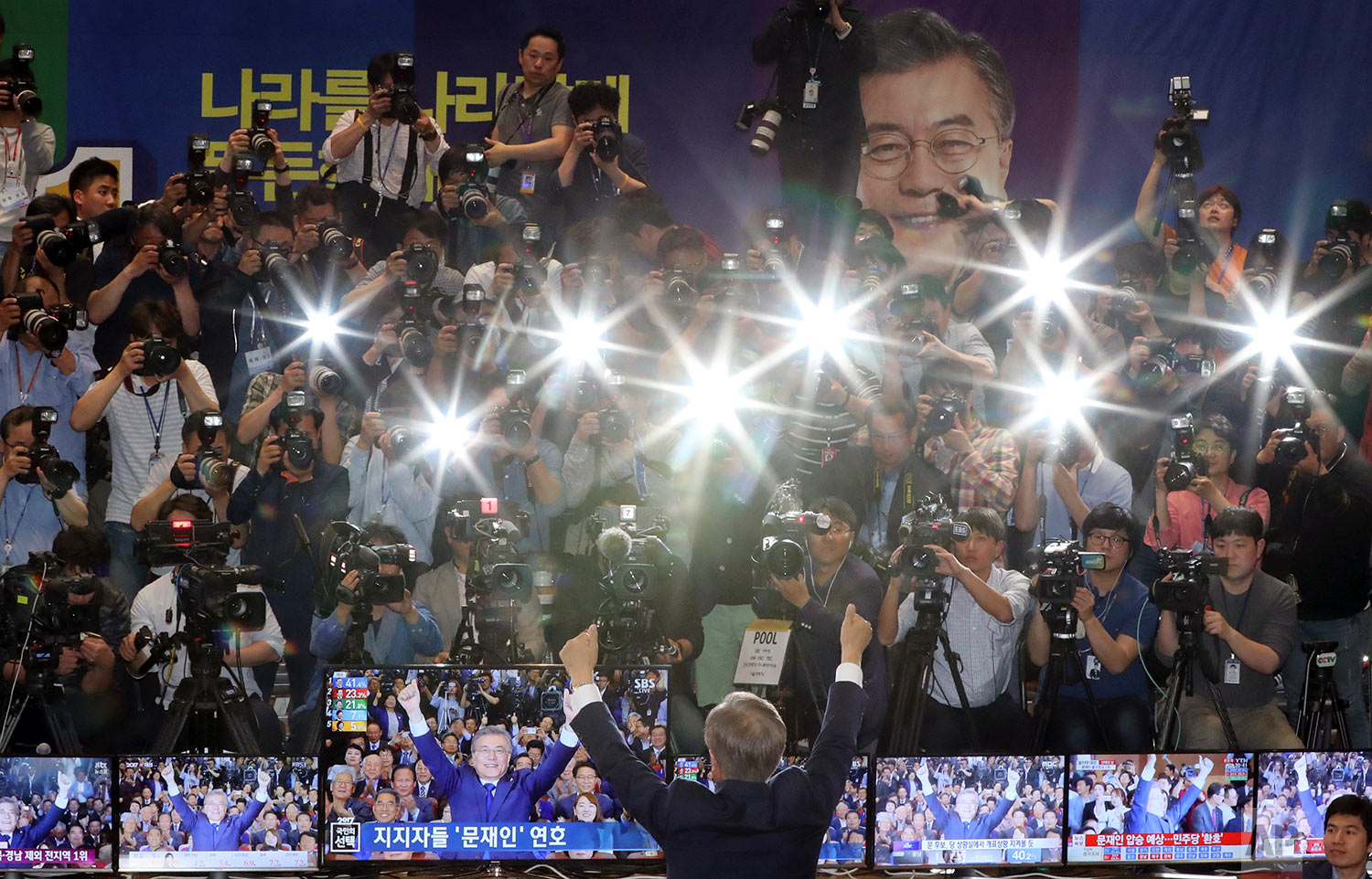 South Korea's presidential candidate Moon Jae-in of the Democratic Party raises his hands in front of the media as his party leaders, members and supporters watch on television local media's results of exit polls for the presidential election at National Assembly in Seoul, South Korea, Tuesday, May 9, 2017. Exit polls forecast that liberal candidate Moon win the election Tuesday to succeed ousted President Park Geun-hye. (AP Photo/Lee Jin-man)