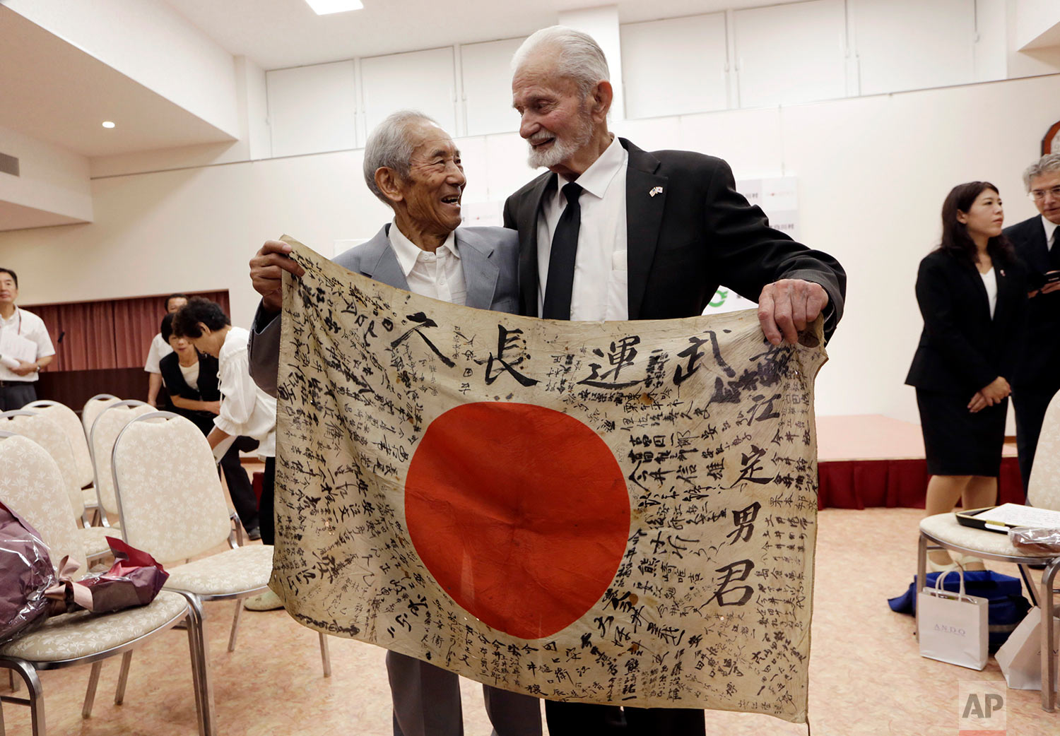 WWII veteran Marvin Strombo, right, and Tatsuya Yasue, 89-year-old farmer, hold a Japanese flag with autographed messages which was owned by his brother Sadao Yasue, who was killed in the Pacific during World Work II, during a ceremony in Higashishirakawa, in central Japan's Gifu prefecture Tuesday, Aug. 15, 2017. Strombo has returned to the fallen soldier's family the calligraphy-covered flag he took from the man's body 73 years ago. (AP Photo/Eugene Hoshiko)