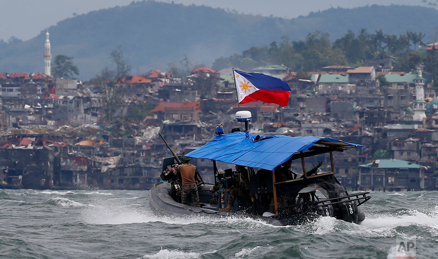 """Philippine Navy commandos aboard a gunboat patrol the periphery of Lake Lanao as smoke rises from the """"Main Battle Area"""" where pro-Islamic group militants are making a final stand amid a massive military offensive of Marawi city in southern Philippines Thursday, Oct. 19, 2017. Two days after President Rodrigo Duterte declared the liberation of Marawi city, the military announced the killing of 13 more suspected militants in the continuing military offensive. (AP Photo/Bullit Marquez)"""