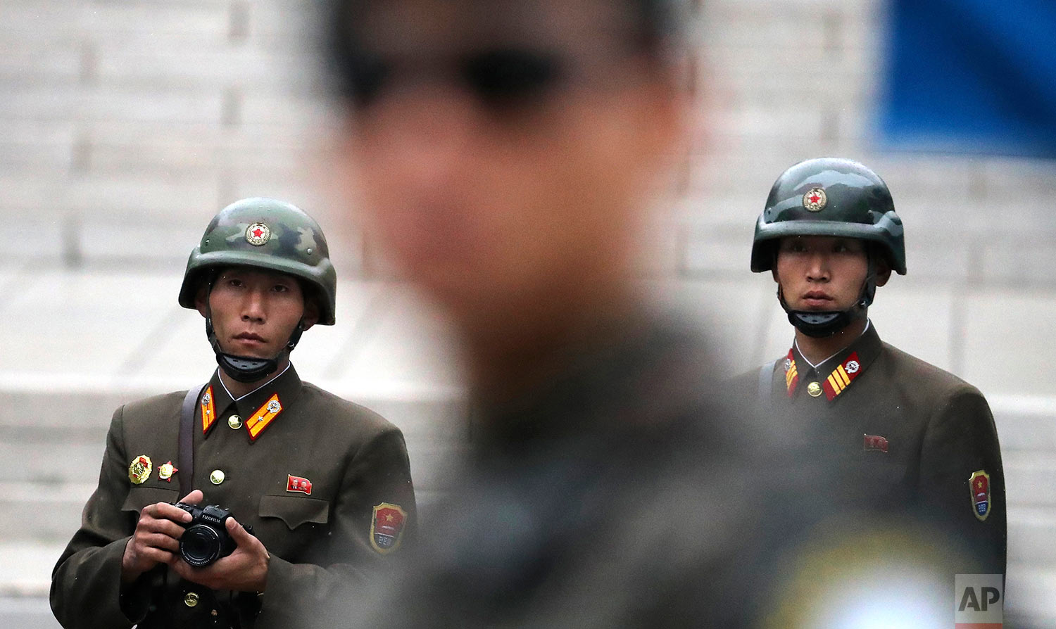In this Monday, April 17, 2017, photo, two North Korean soldiers look at the south side as a South Korean soldier, center, stand guard while U.S. Vice President Mike Pence visited the border village of Panmunjom which has separated the two Koreas since the Korean War, South Korea. (AP Photo/Lee Jin-man)