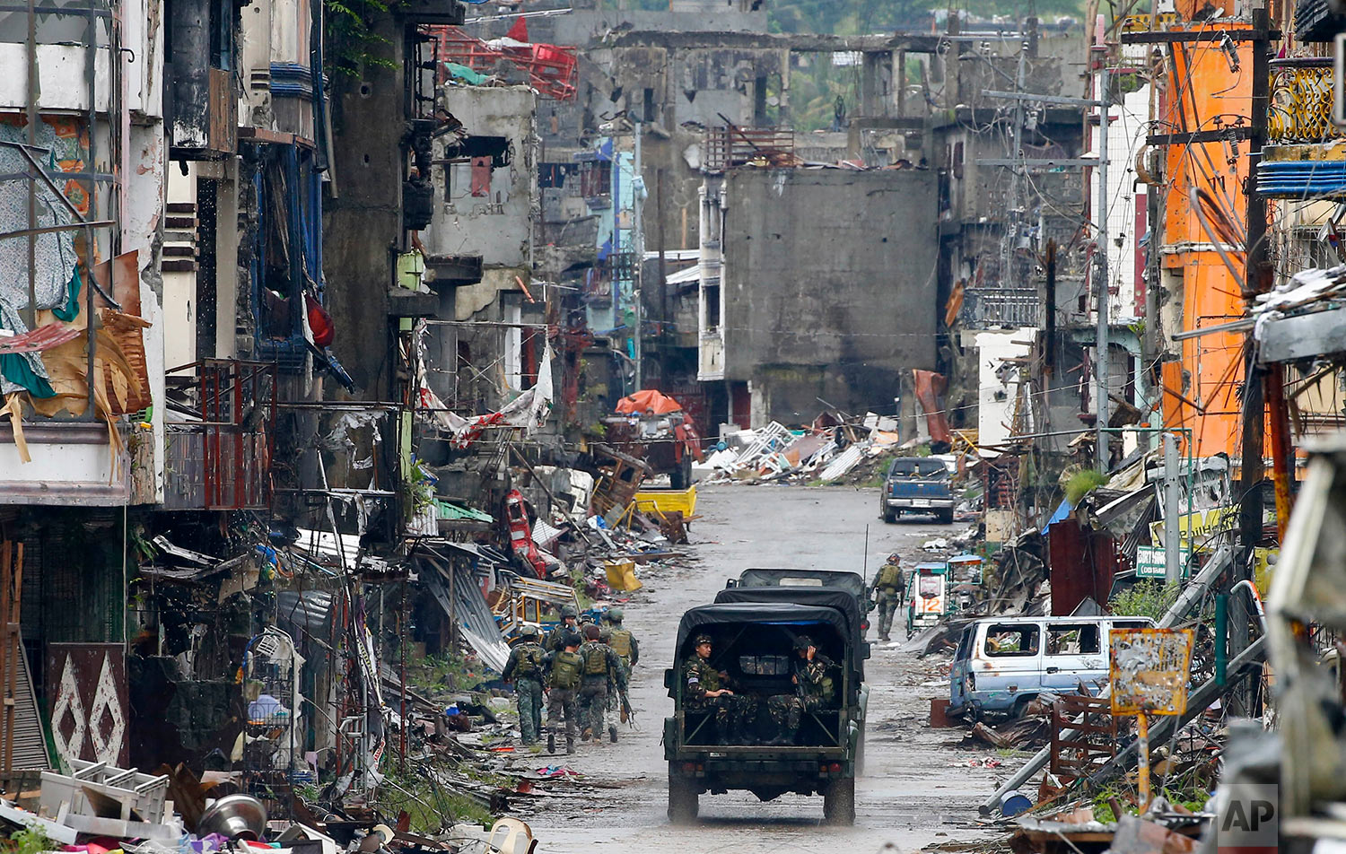 """Amidst the ruins at """"Ground Zero"""" Philippine troops return to their deployment after attending the ceremony wherein President Rodrigo Duterte declared the liberation of Marawi city in southern Philippines after almost five months of the siege by pro-Islamic State group militants Tuesday, Oct. 17, 2017. Gunfire rang out sporadically and explosions thudded as Philippine soldiers fought Tuesday to gain control of the last pocket of Marawi controlled by Islamic militants as President Duterte declared the southern city liberated from """"terrorist influence."""" (AP Photo/Bullit Marquez)"""