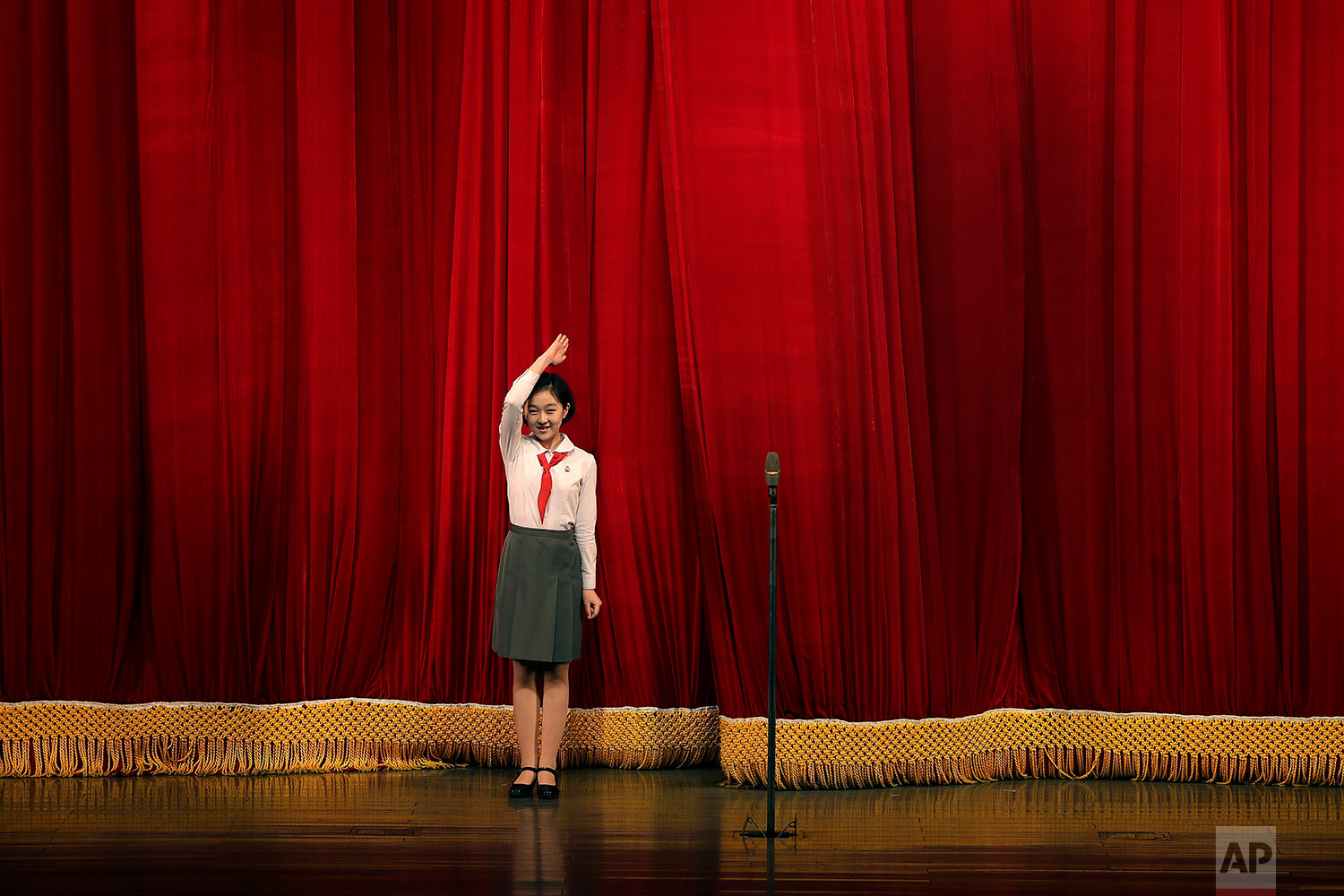 A North Korean student salutes the audience at the start of a performance at the Mangyongdae Children's Palace on Friday, April 14, 2017, in Pyongyang, North Korea. Amid rising regional tensions, Pyongyang residents have been preparing for North Korea's most important holiday: the 105th birth anniversary of Kim Il Sung, the country's late founder and grandfather of current ruler Kim Jong Un. (AP Photo/Wong Maye-E)